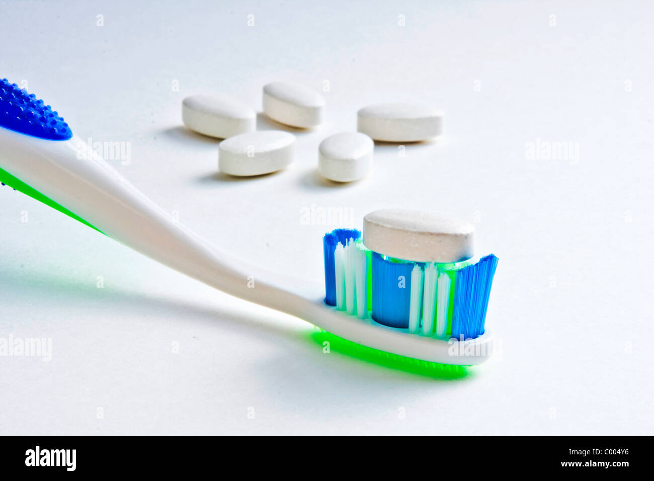 Calcium tablet resting on toothbrush bristles with other tablets in background - Stock Image