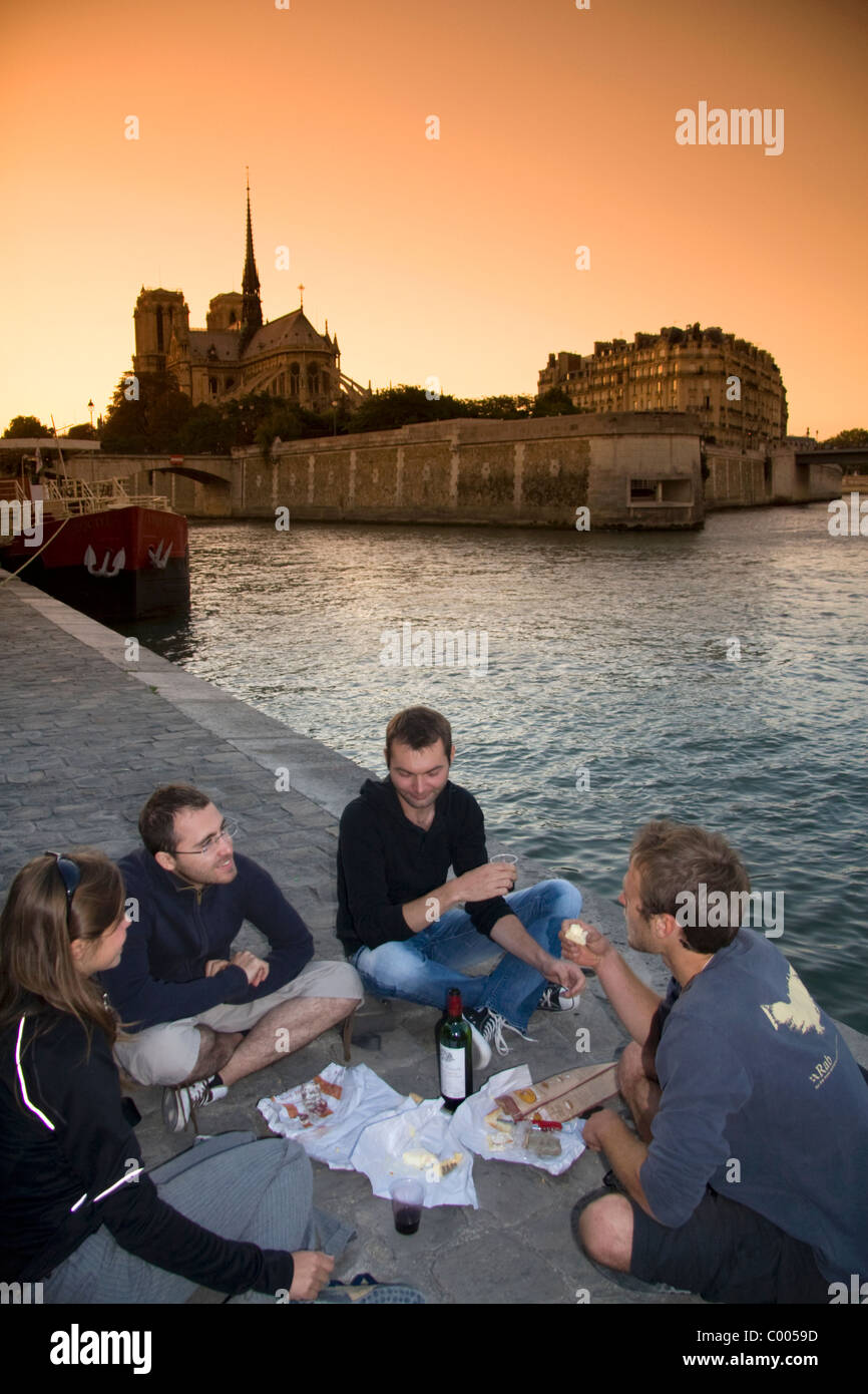 Parisians picnicking along the River Seine at sunset in Paris, France. - Stock Image