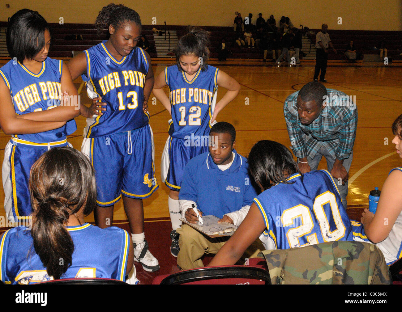 Coach discusses strategy with his players at a girl's high school basketball game - Stock Image
