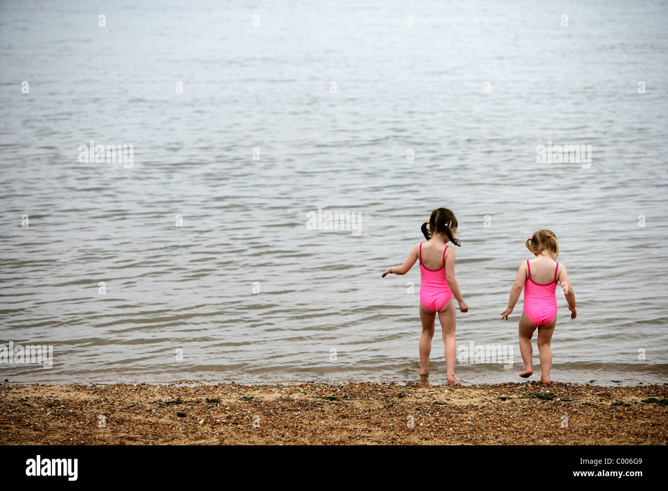 Sisters In Matching Pink Bathing Suits Playing On Beach - Stock Image