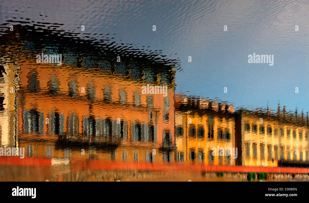 Reversed reflection of house in Florence, reflected on the surface of Arno River. - Stock Image
