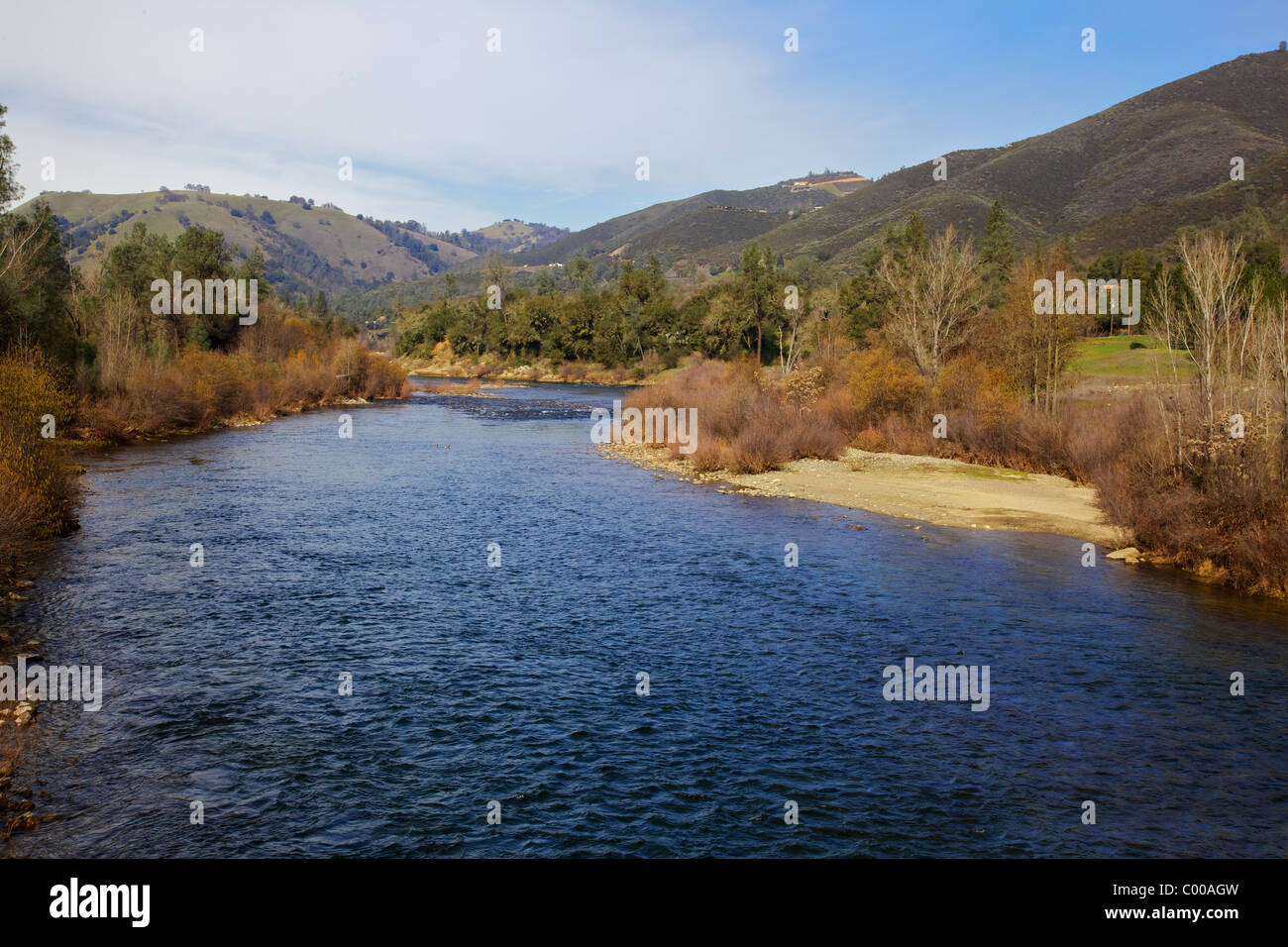 Curving blue water of the coloma river with green hills and blue sky backround Stock Photo