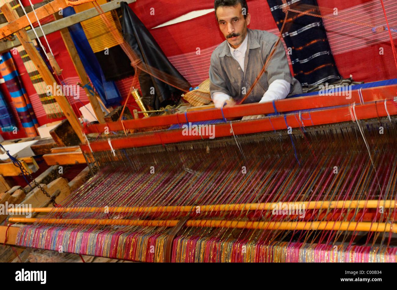 Weaver operating a horizontal wooden hand loom in a cloth shop Fes el Bali Medina Fez Morocco - Stock Image