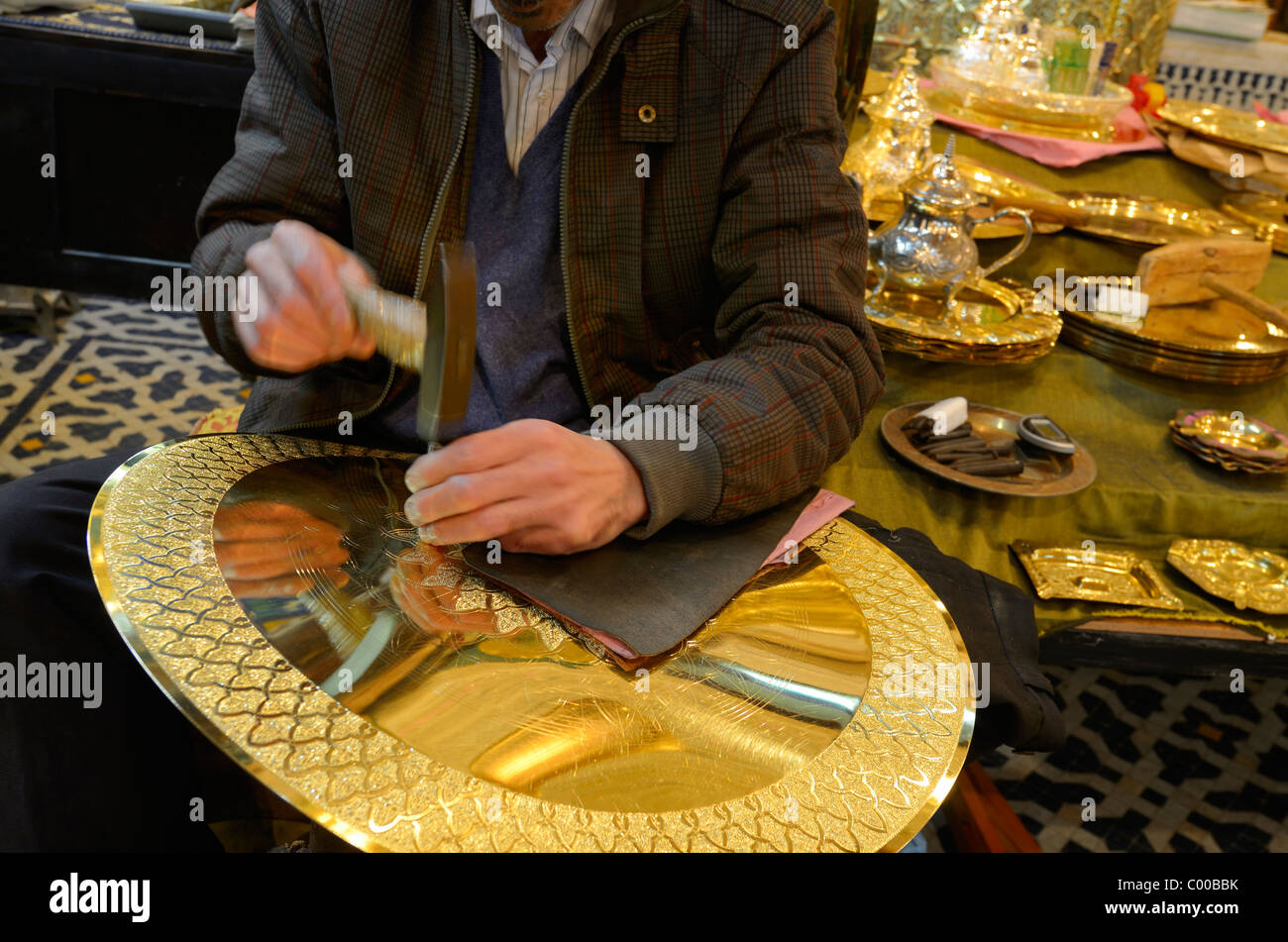 Worker with hammer and chisel engraving complex patterns on brass plate in Fes el Bali Fez Morocco - Stock Image