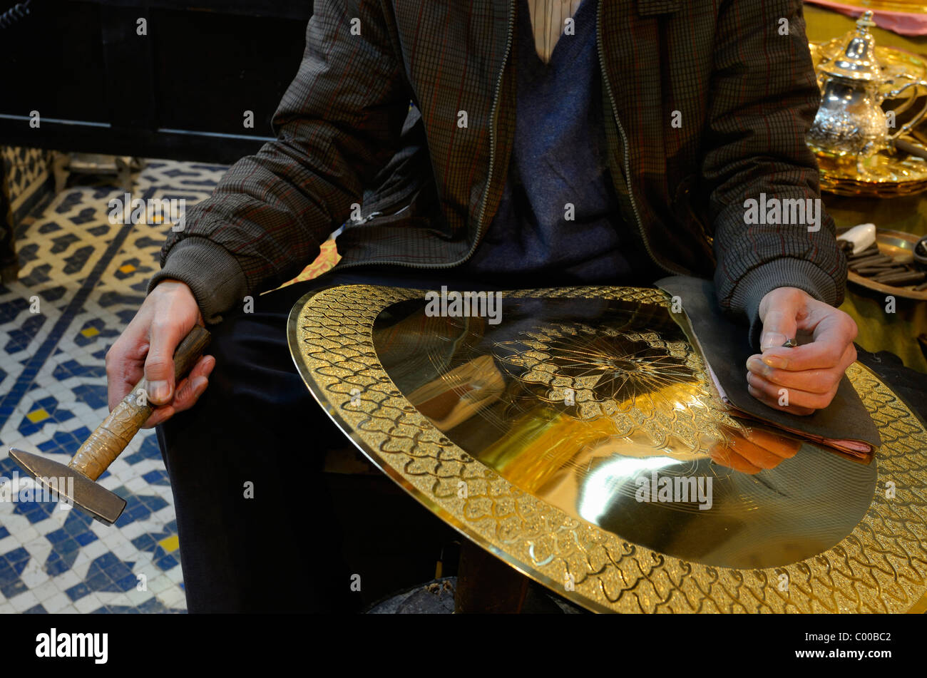 Worker with hammer and chisel showing work in progress engraving brass plate in Fes el Bali Fez Morocco - Stock Image