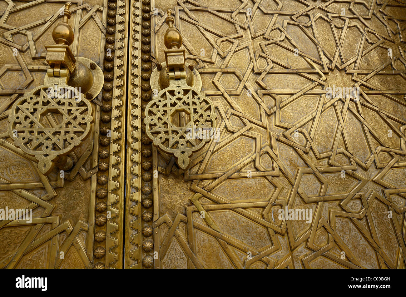 Close up of detailed engraving and knockers on the brass doors to the Dar El Makhzen palace in Fes Morocco - Stock Image