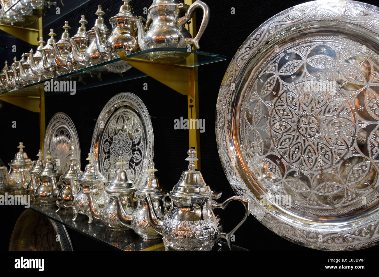 Metalware shop with silver teapots and plates with intricate design engraving Fez Morocco - Stock Image