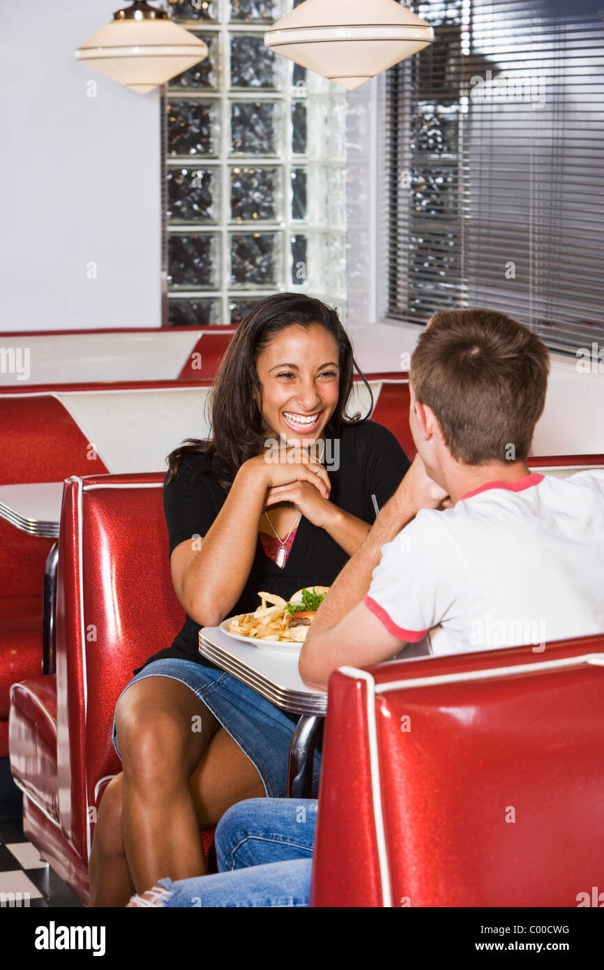 Teenage interracial couple having lunch in a diner Stock Photo