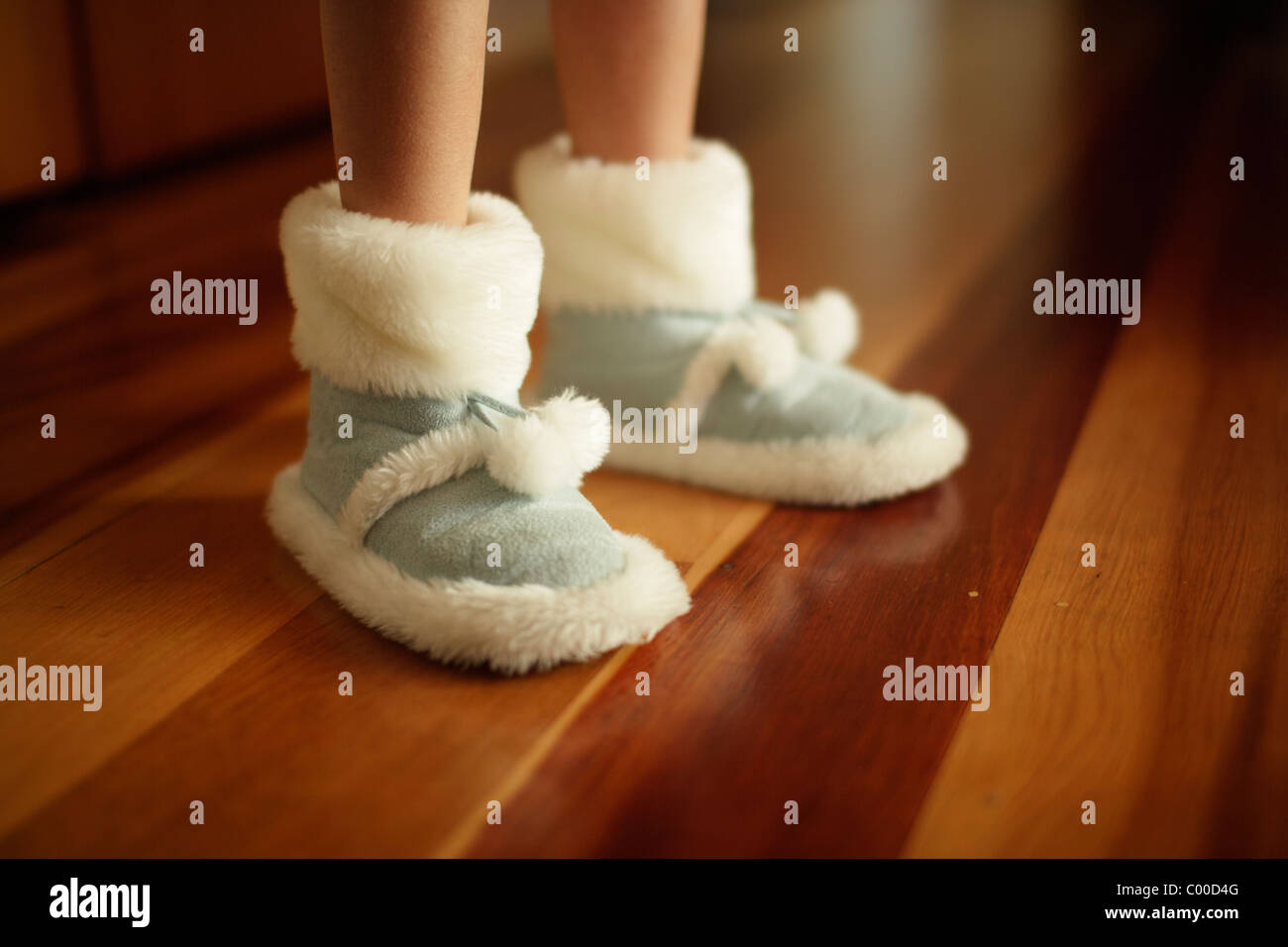Girl's warm slippers on wooden floor made from synthetic sheepskin - Stock Image