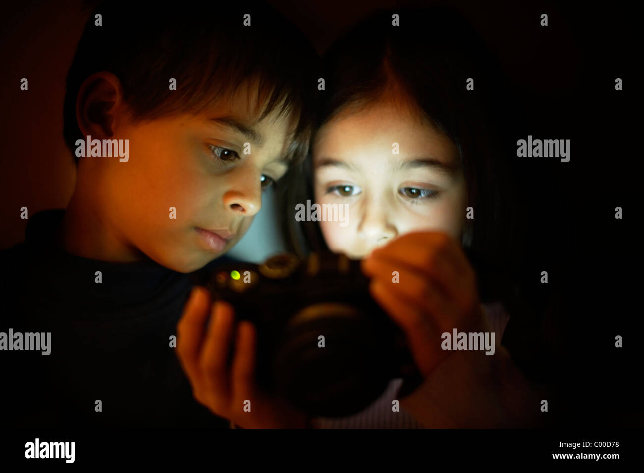 Boy and girl look at digital camera screen - Stock Image