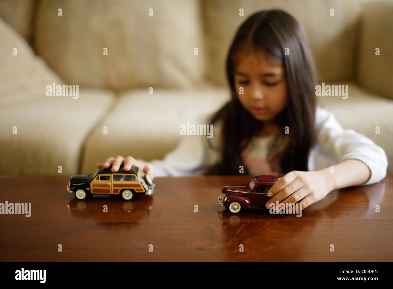 Girl plays with toy cars - Stock Image