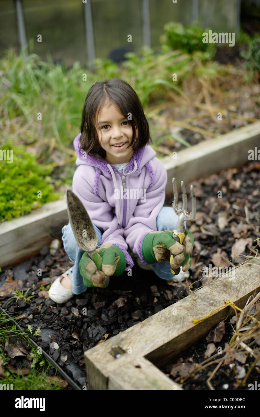 Girl with fork, trowel and large gardening gloves beside organic vegetable plot - Stock Image