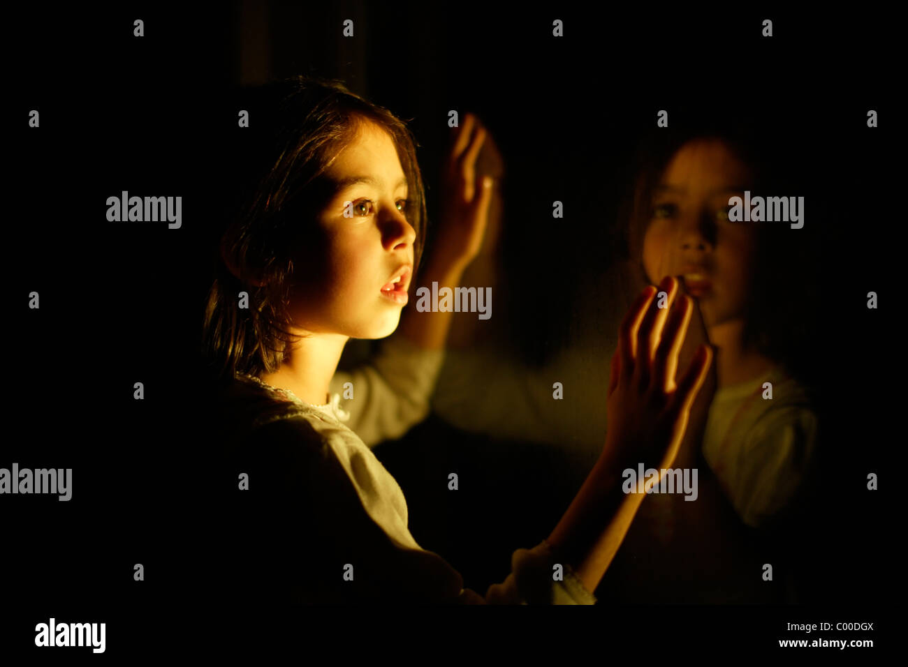 Girl at night with window reflection - Stock Image