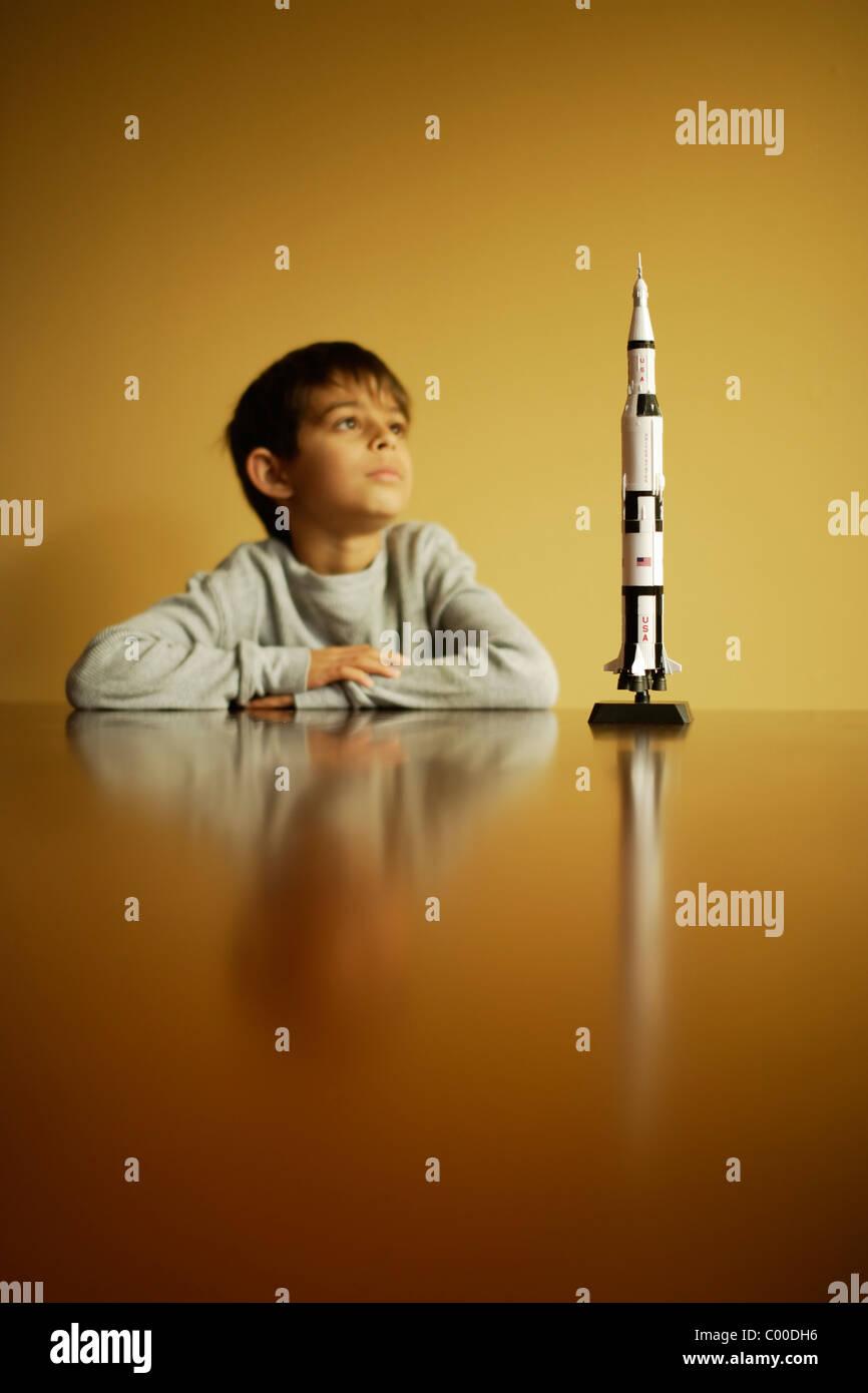Boy with model Saturn V Apollo moon rocket - Stock Image