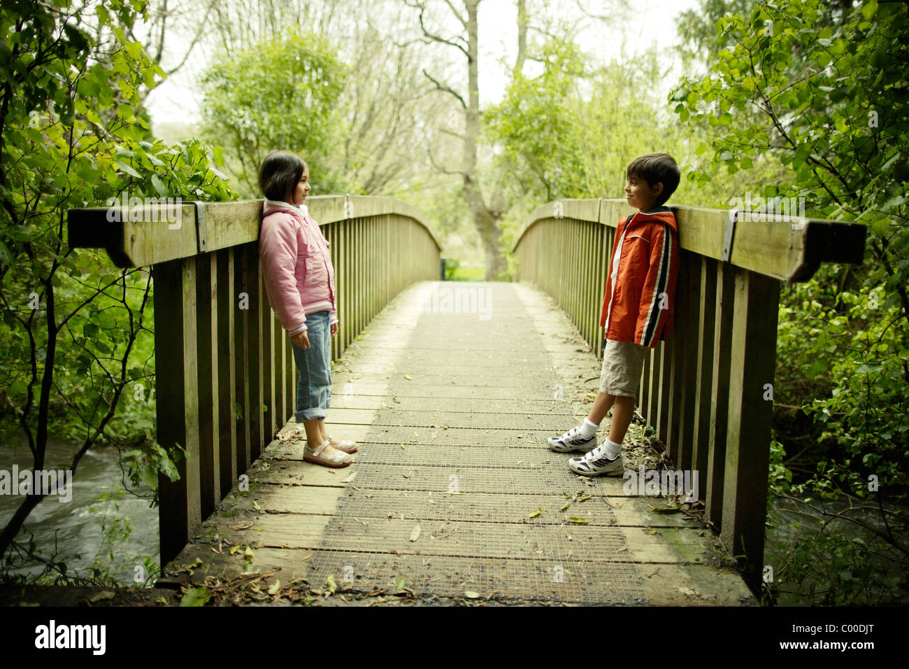 Boy and girl look at each other on wooden bridge. - Stock Image