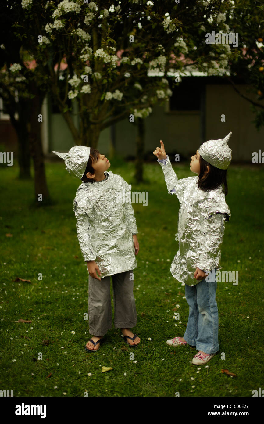 Children wear protective baking foil whilst watching out for possible alien invasion. - Stock Image