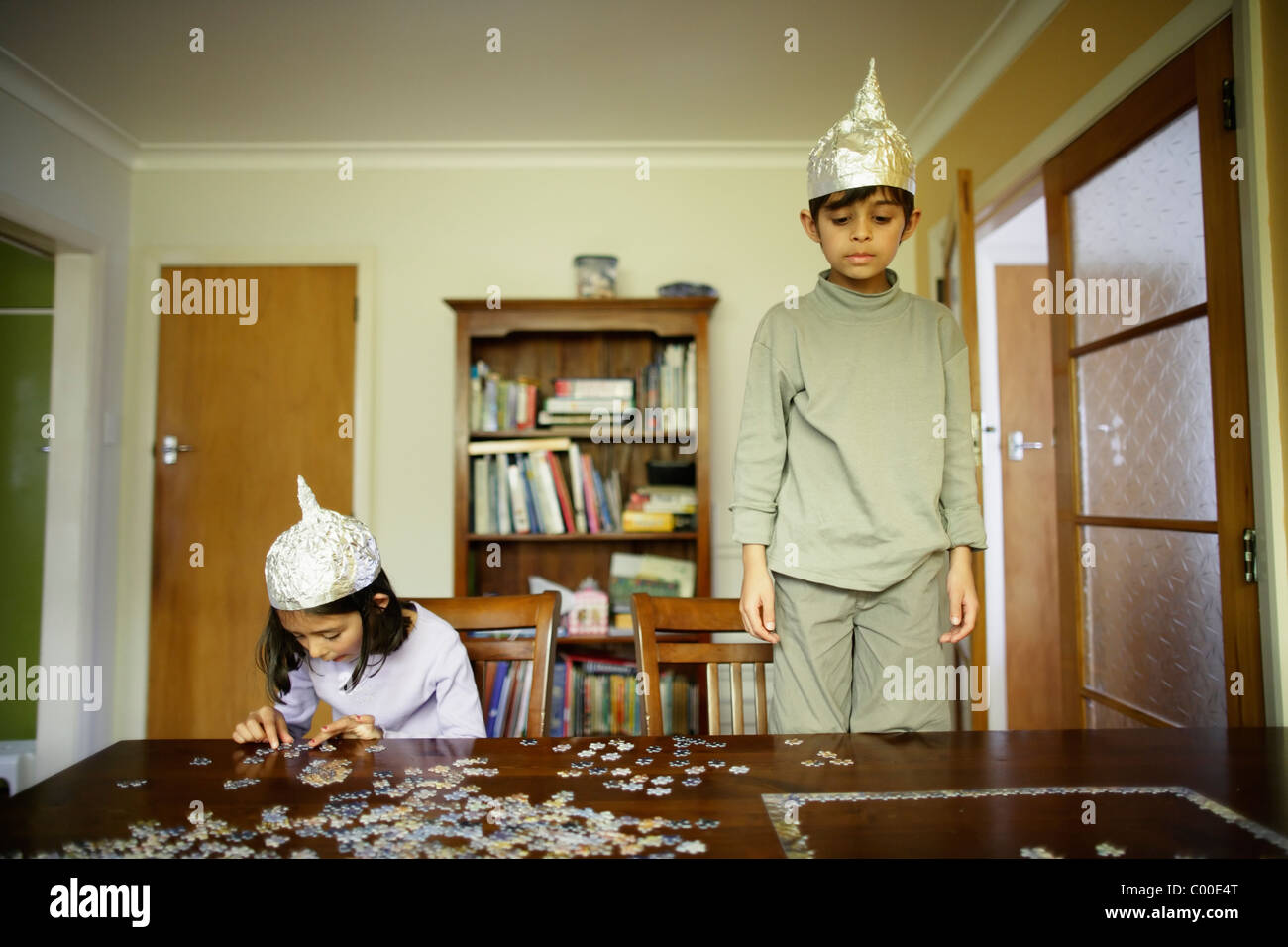 Attempting the jigsaw with foil hats. - Stock Image