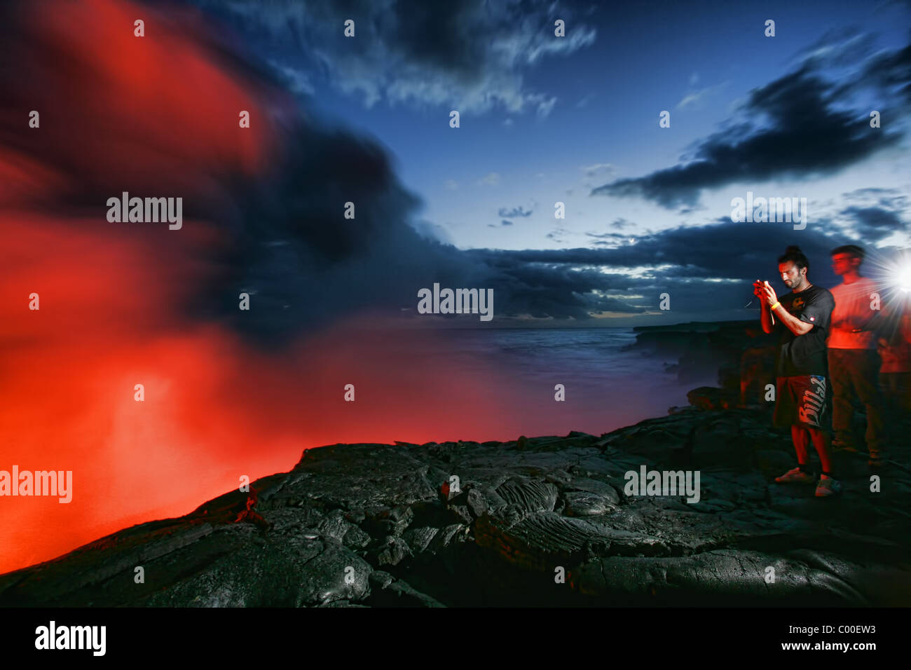 Tourists watching the Kilauea Lava flow on Hawaii's big island. - Stock Image