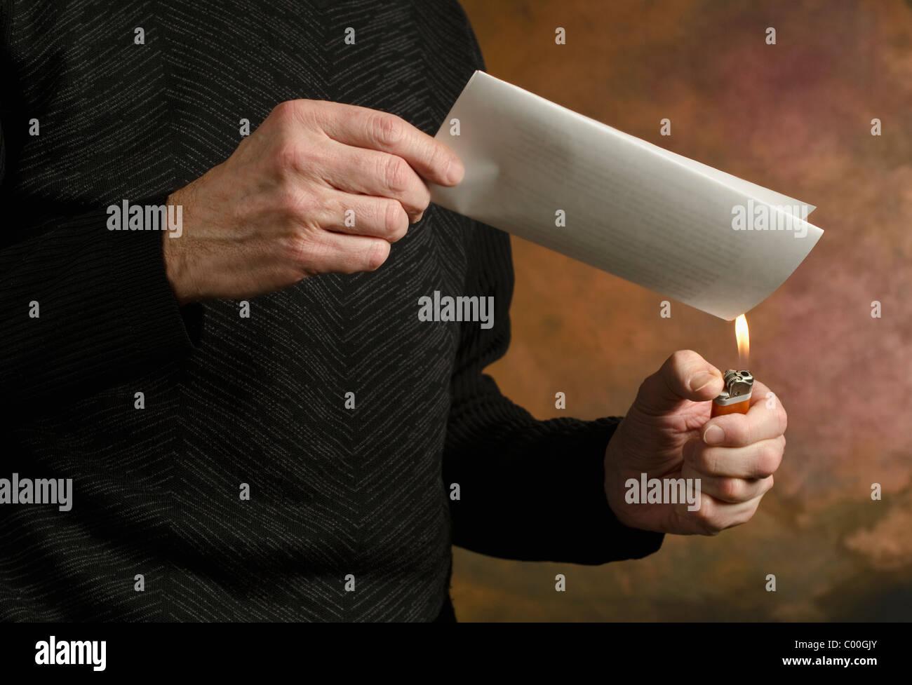 man holding butane lighter to folded document - Stock Image