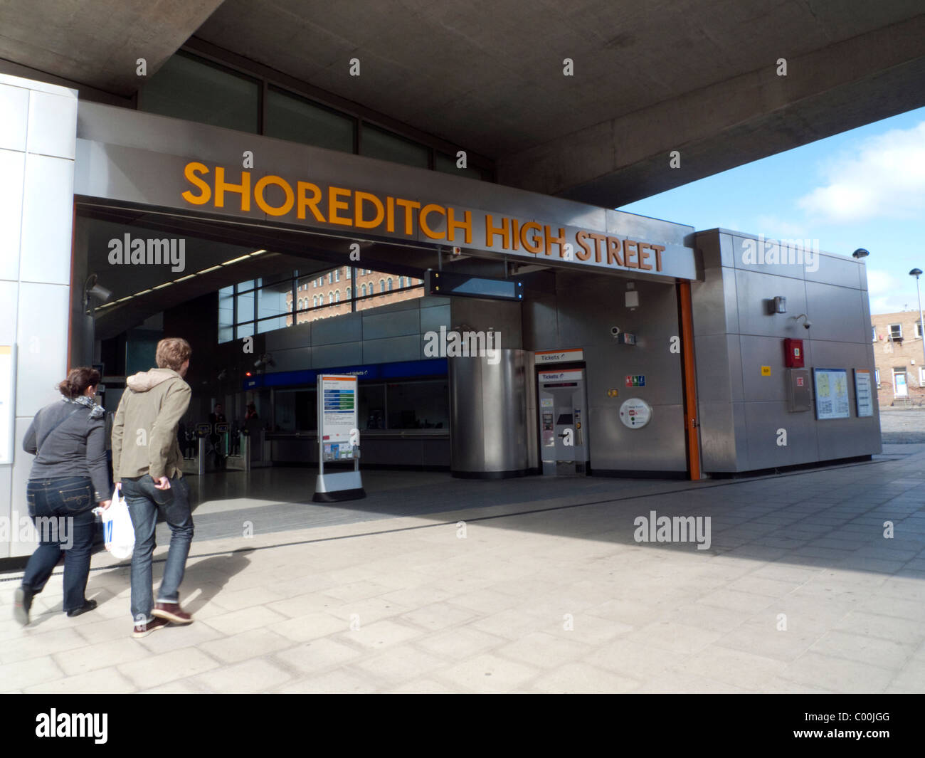 A young couple approaching the entrance to Shoreditch High Street Overground Station East End London England UK - Stock Image