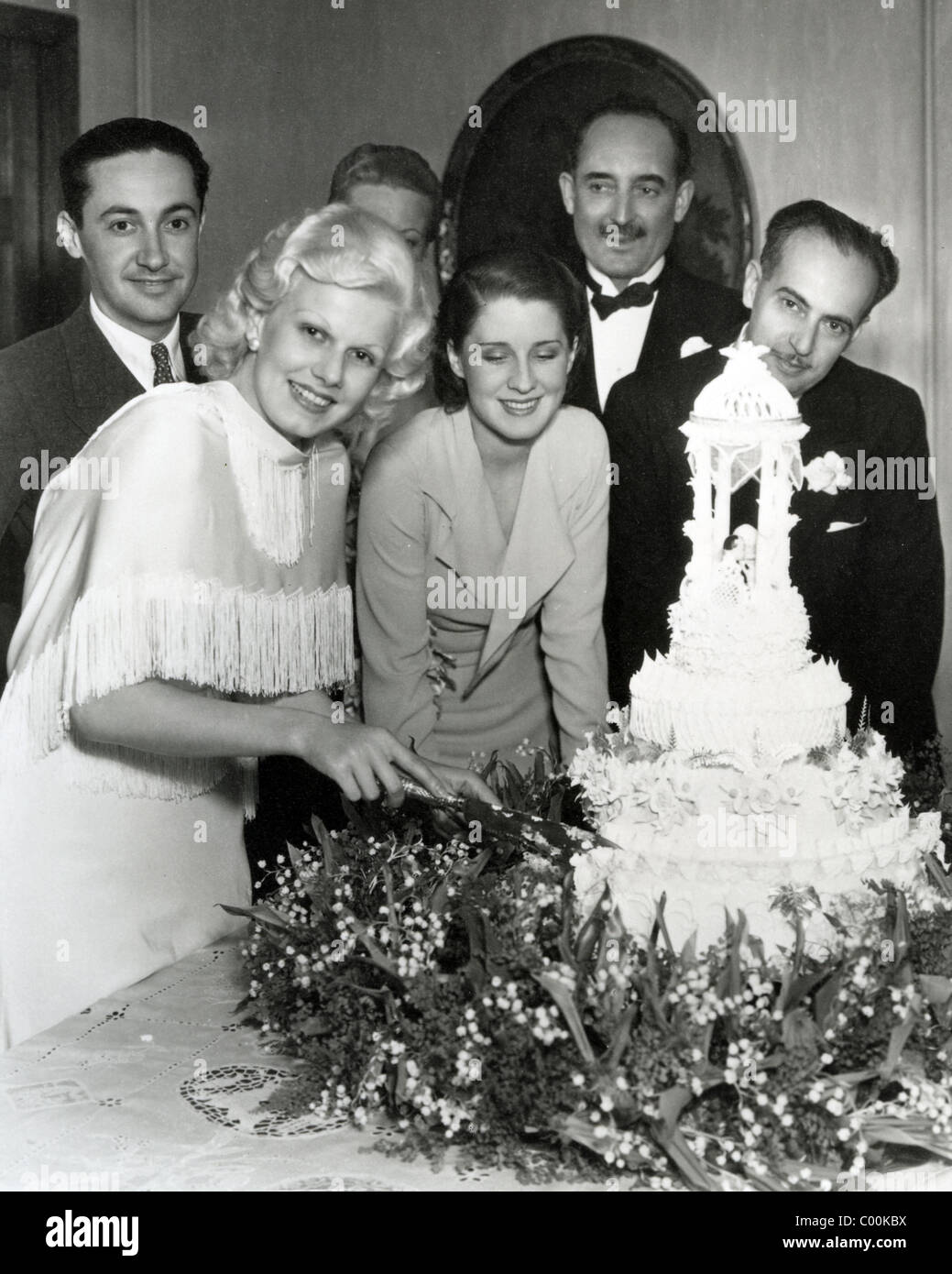 JEAN HARLOW cuts the cake at her wedding to Paul Bern at right 2 July 1932. Irving Thalberg at left and Marino Bello - Stock Image