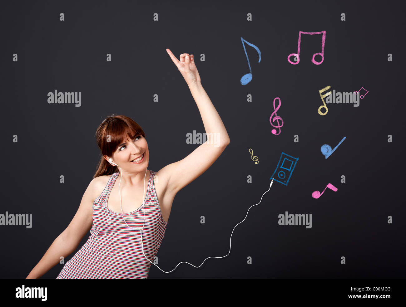 Young woman dancing and listen music with musical notes drawn with chalk on a black wall - Stock Image