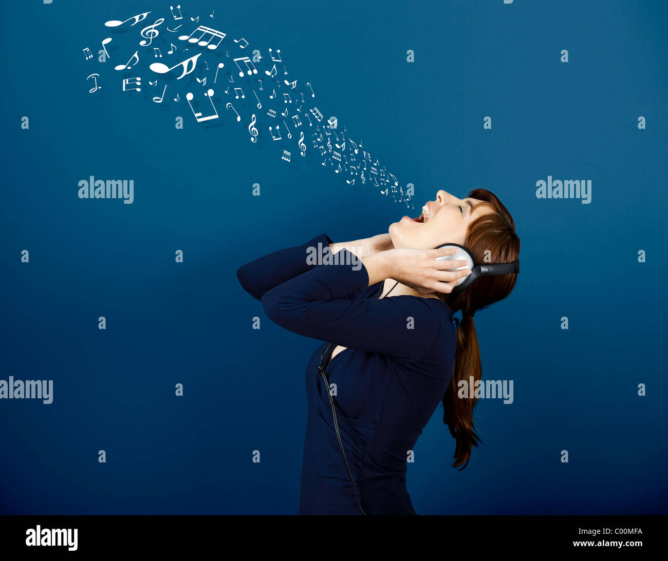 Young woman singing and listen music with musical notes getting out of her mouth - Stock Image