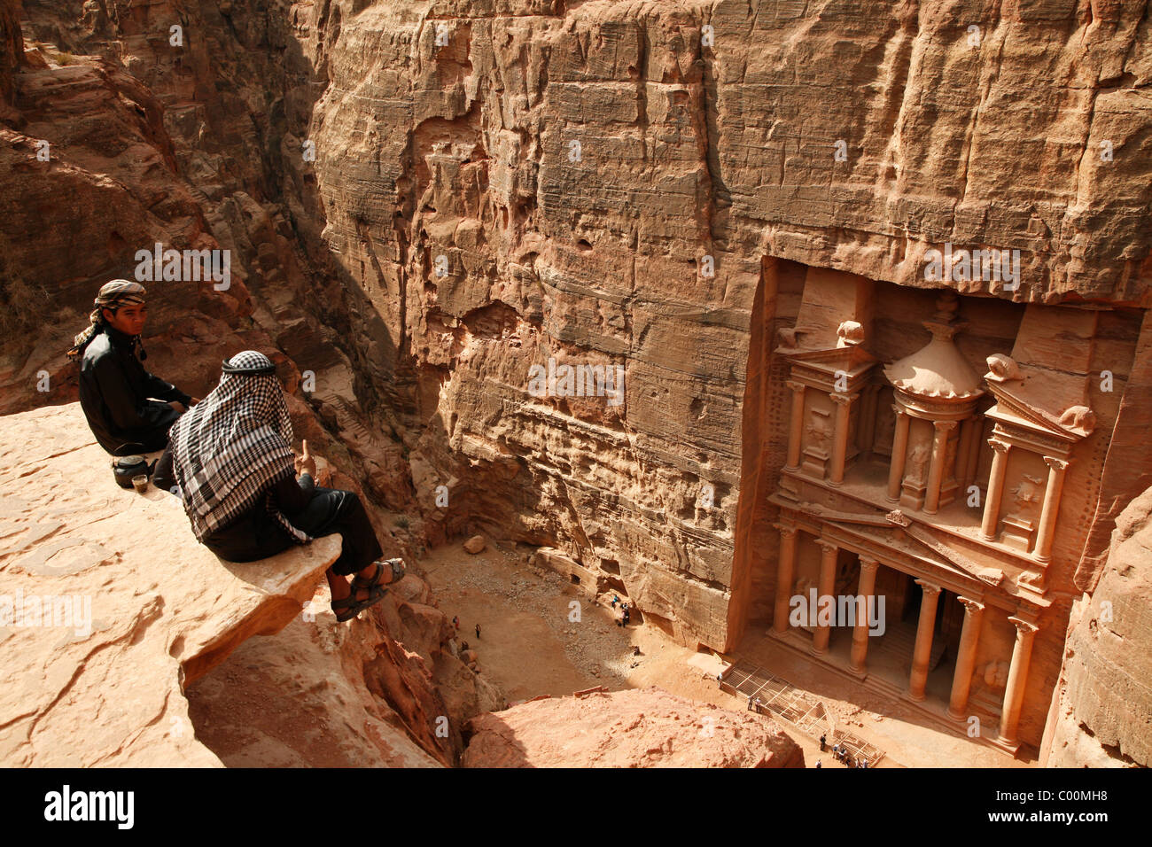 Bedouins sitting on top of a cliff looking down to the Treasury (El Khazneh), Petra, Jordan. - Stock Image