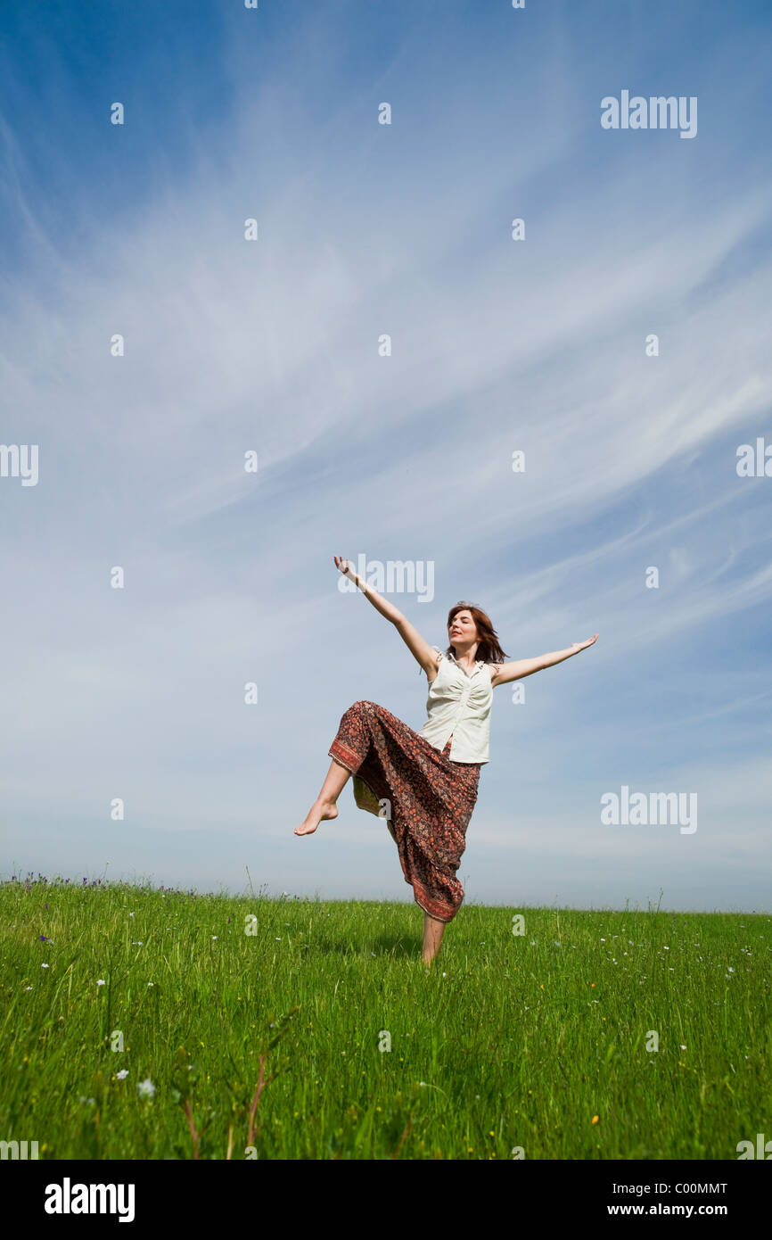 Young woman making dancing poses on a beautiful green meadow Stock Photo