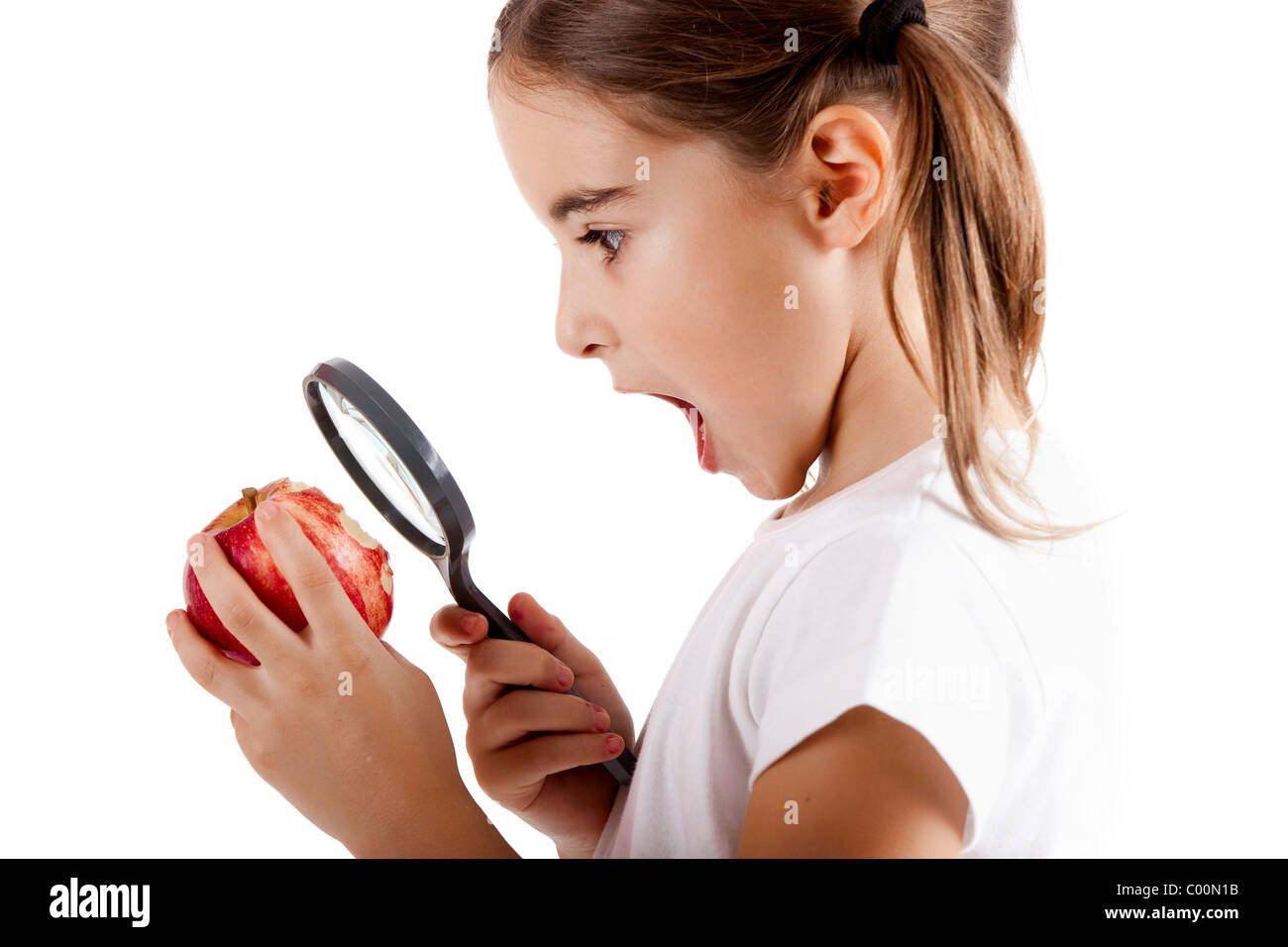 Little girl with a magnifying glass inspecting microbes on a red apple - Stock Image
