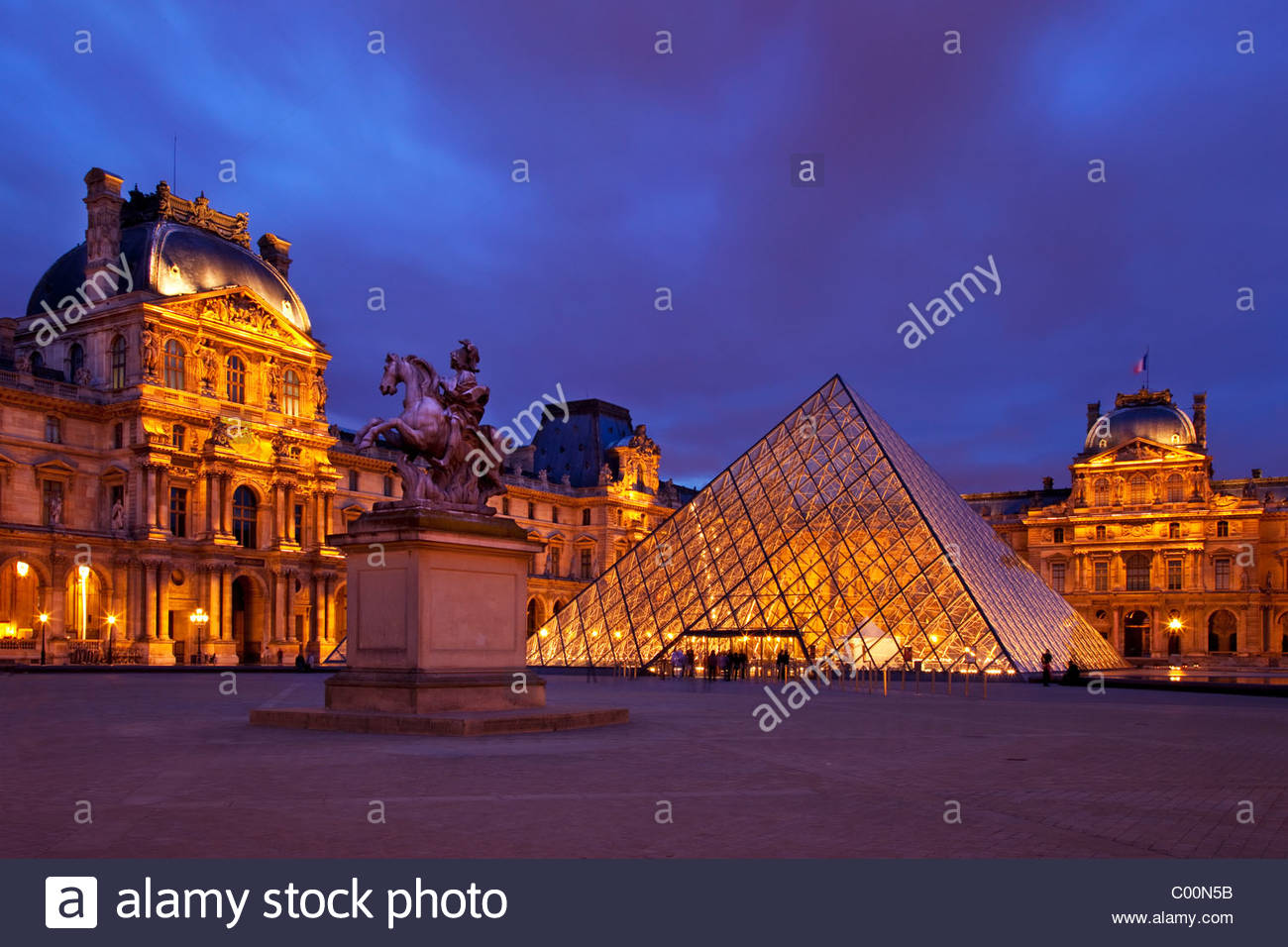 Musee du Louvre with Bernini's statue of King Louis XIV at twilight, Paris France - Stock Image