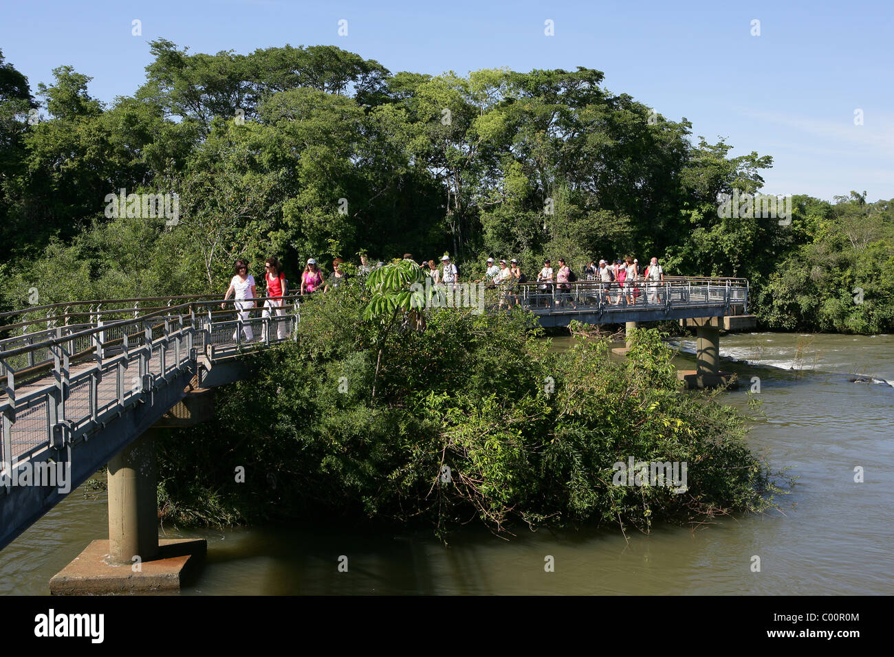 Tourists on raised walkway over [Rio Iguazu] near Garganta del Diabolo [Devil's Throat] at [Iguassu Falls] - Stock Image
