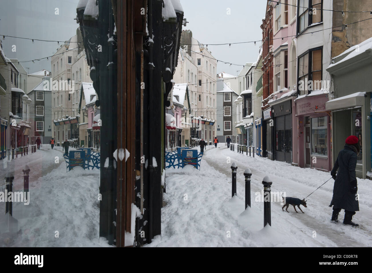 A woman walks her dog along snow covered George Street Old Town Hastings East Sussex England UK Stock Photo