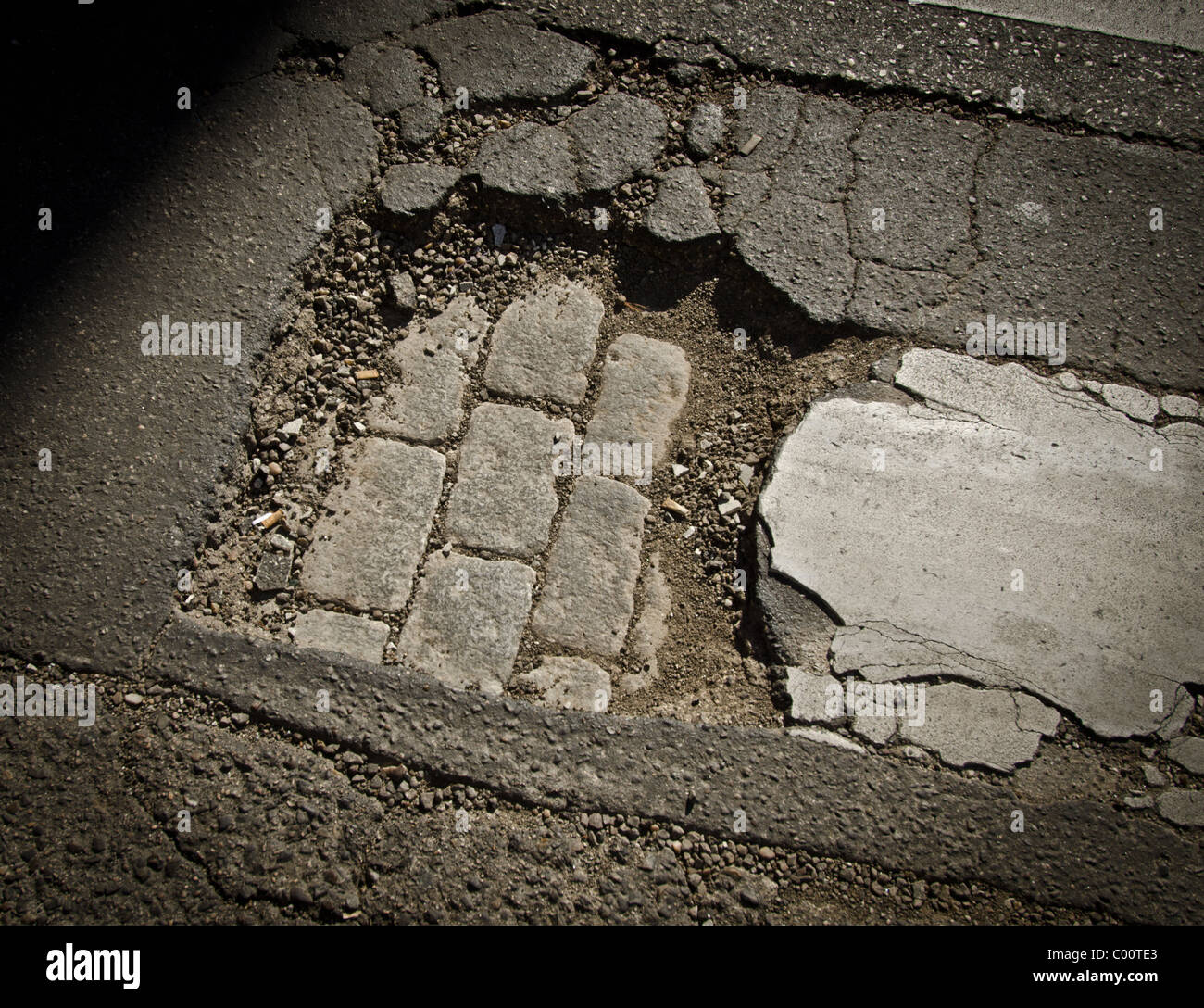 Damaged road surface showing different layers of surfaces Stock Photo