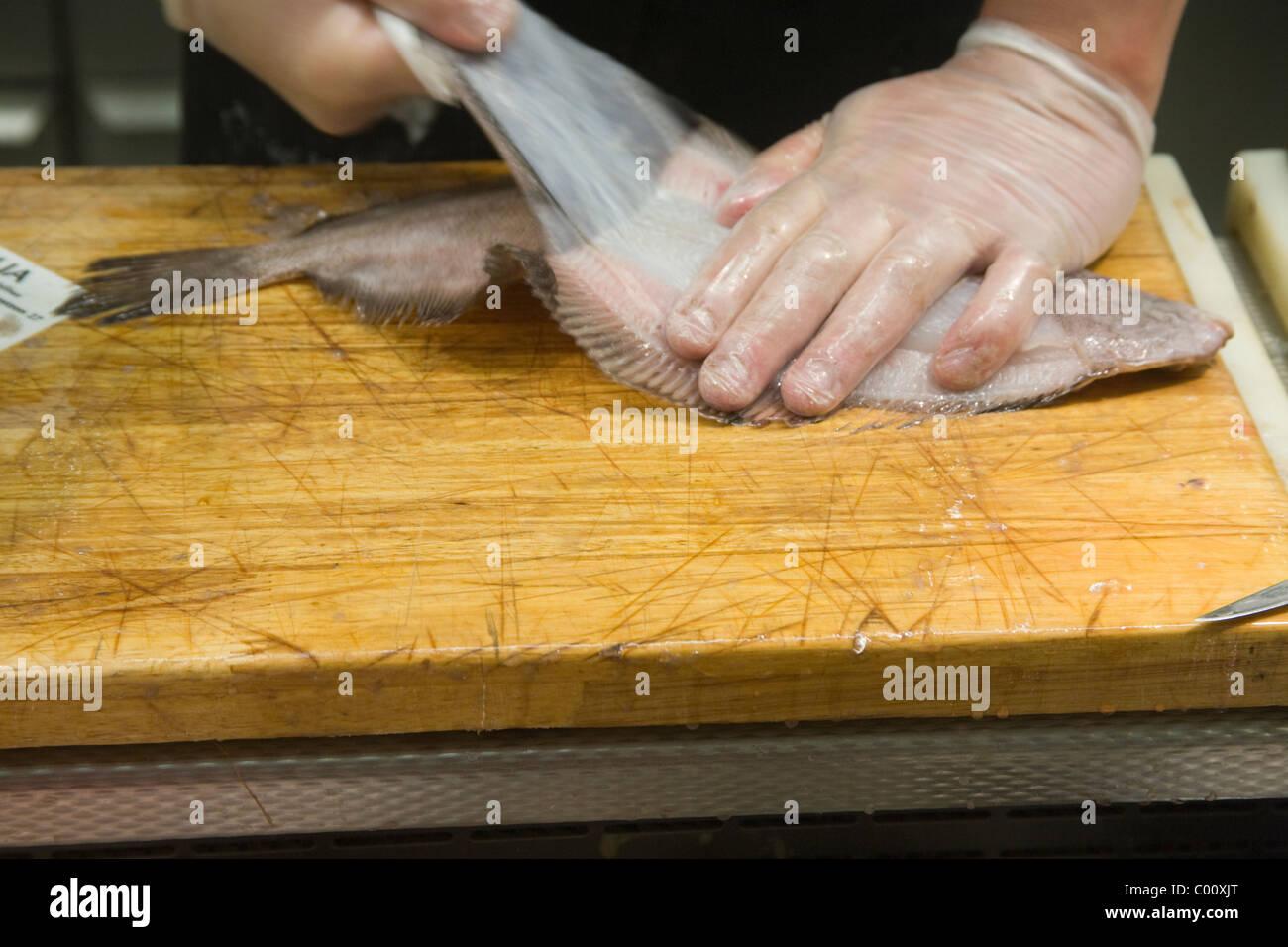 Fish Gutting Gutting Glyptocephalus cynoglossus Witch flounder Torbay sole Market-hall - Stock Image