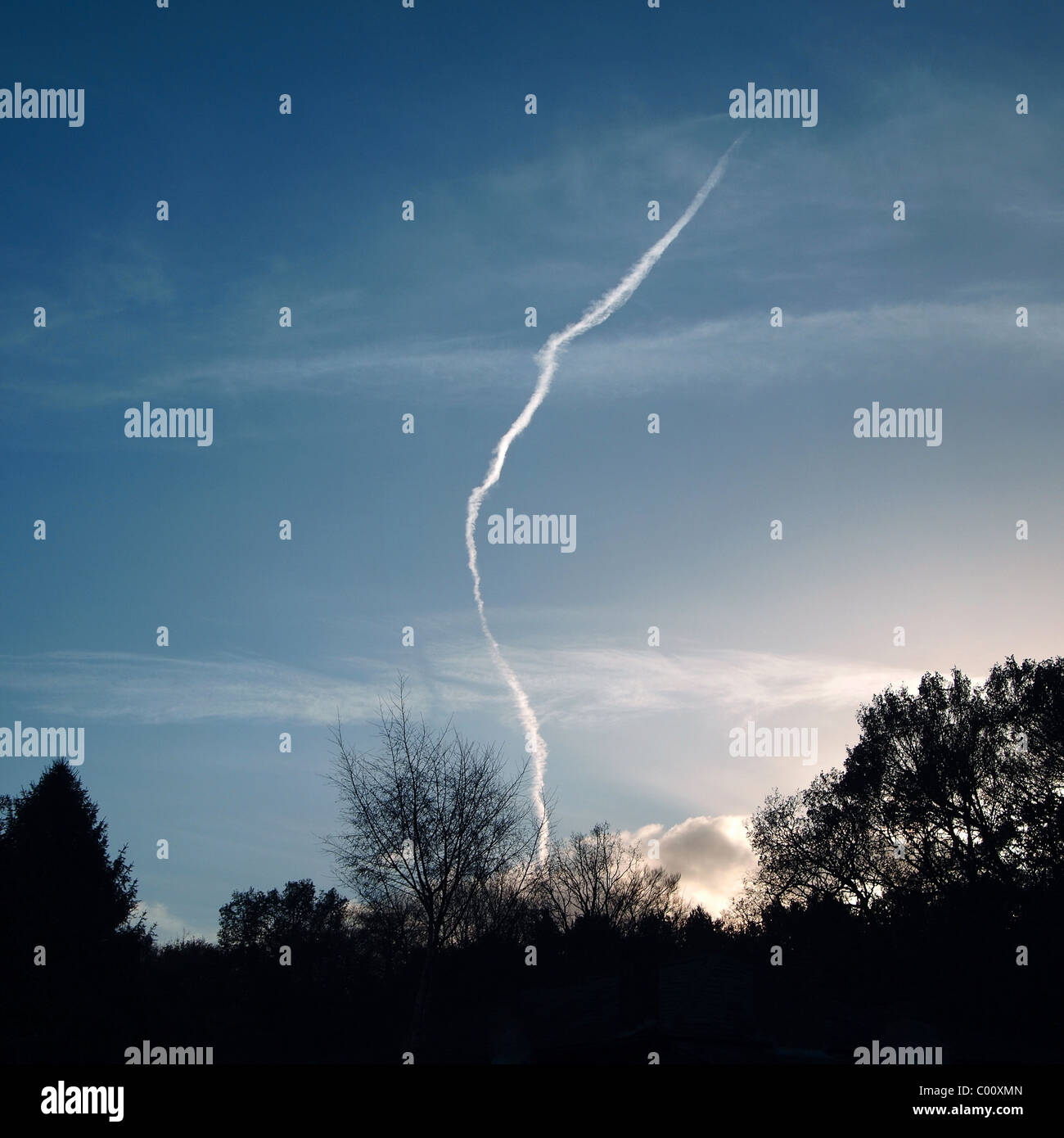 landscape image of a jet trail looking like lightning with setting sun Stock Photo