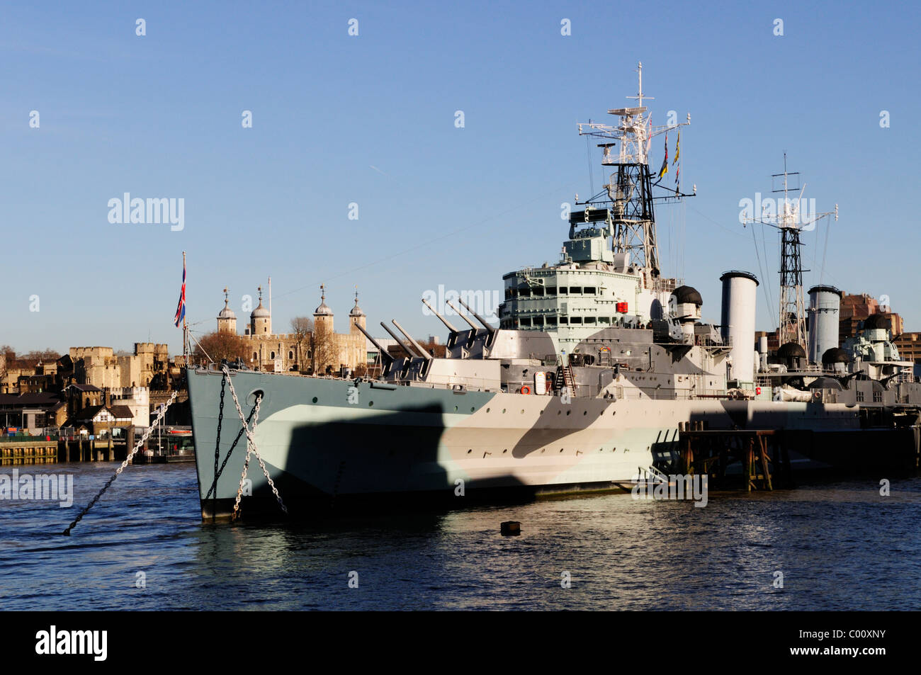 HMS Belfast with the Tower of London in the background, London, England, Uk - Stock Image