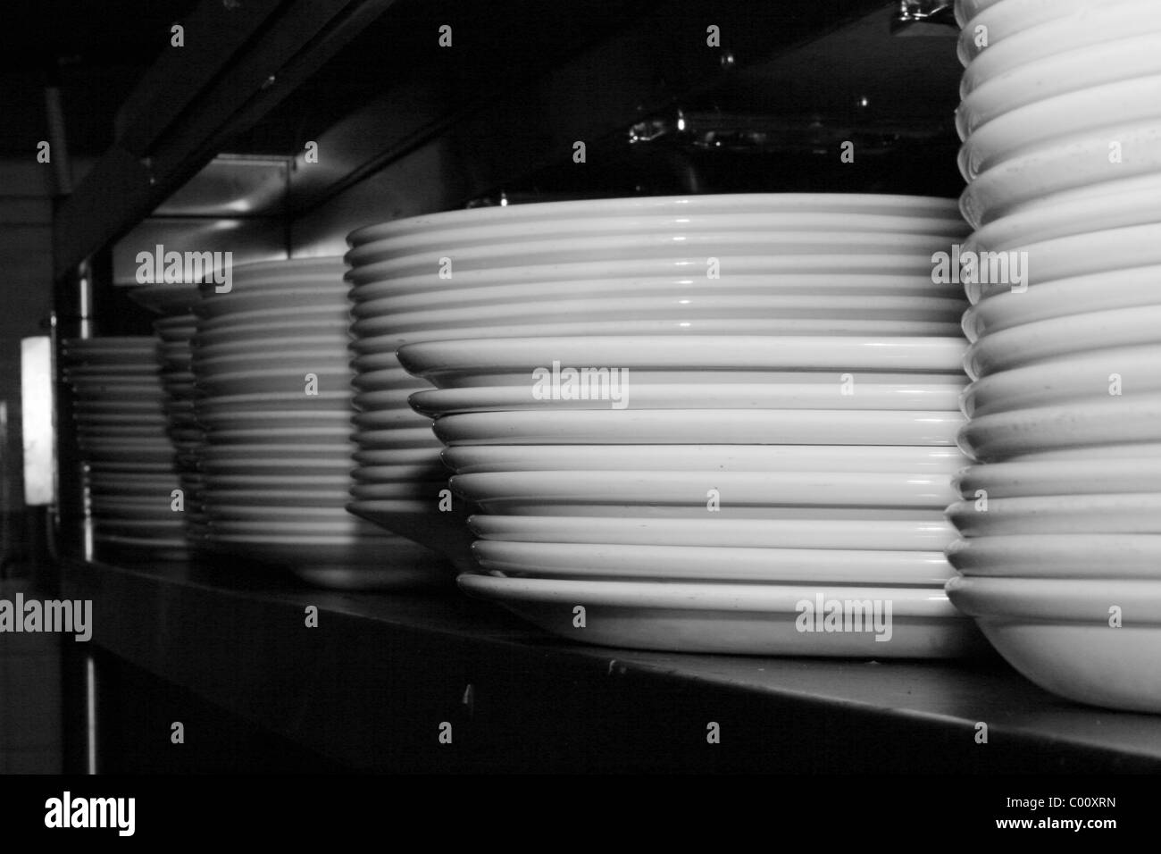 stacked plates on shelf in kitchen - Stock Image