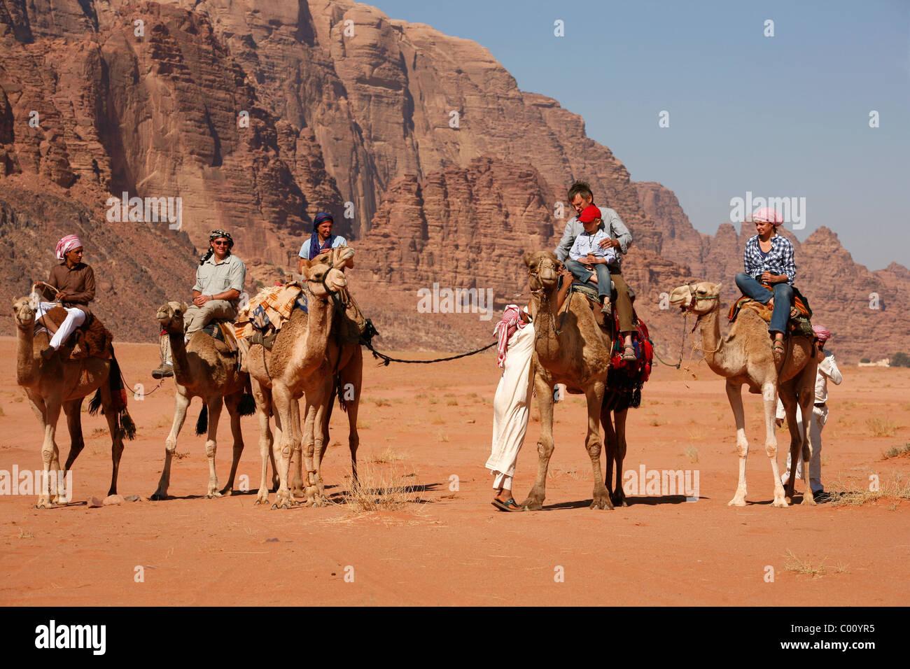 Tourists riding camels in the desert, Wadi Rum, Jordan. - Stock Image