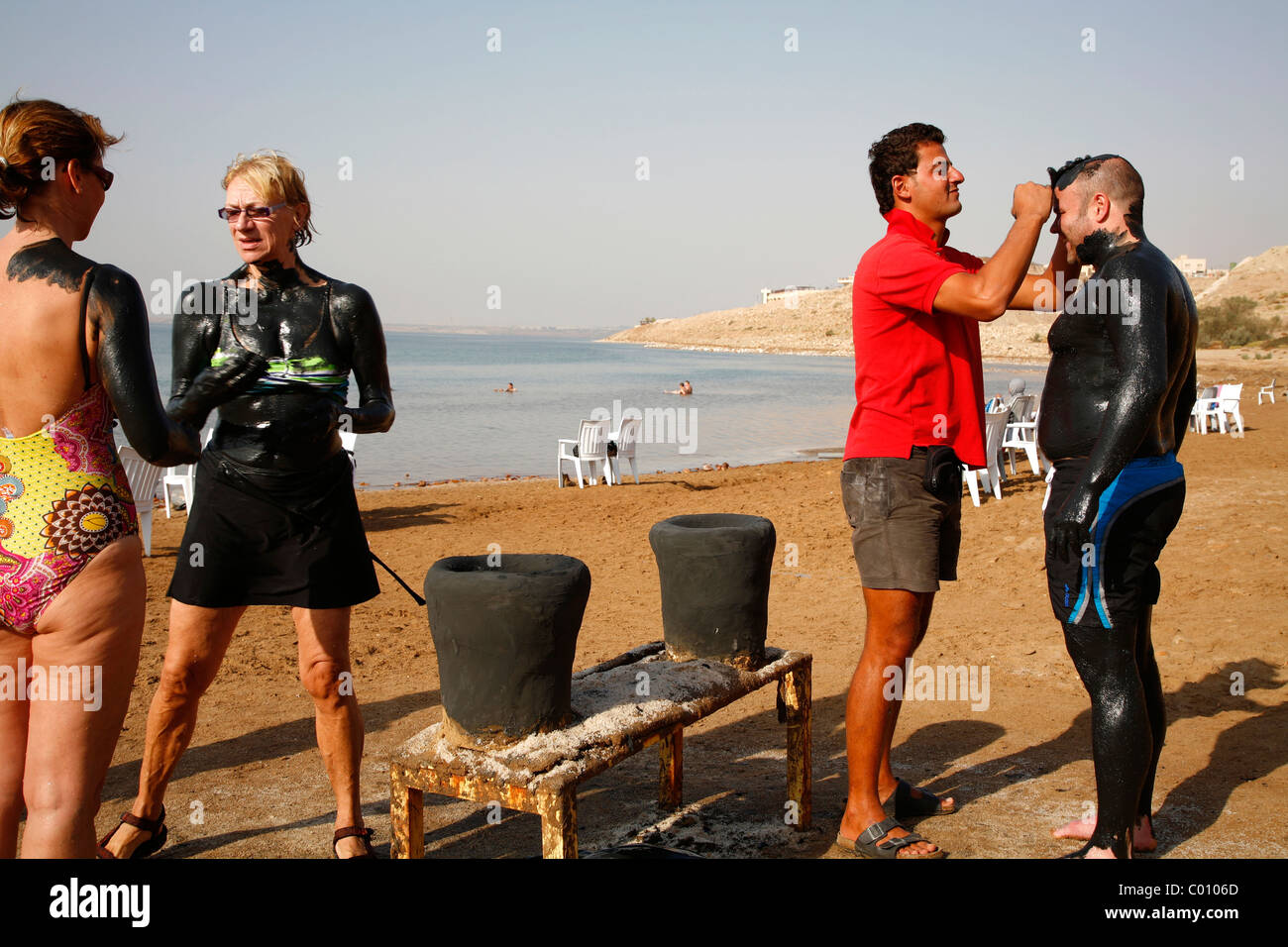 People covered with mud at the dead sea, Jordan. - Stock Image
