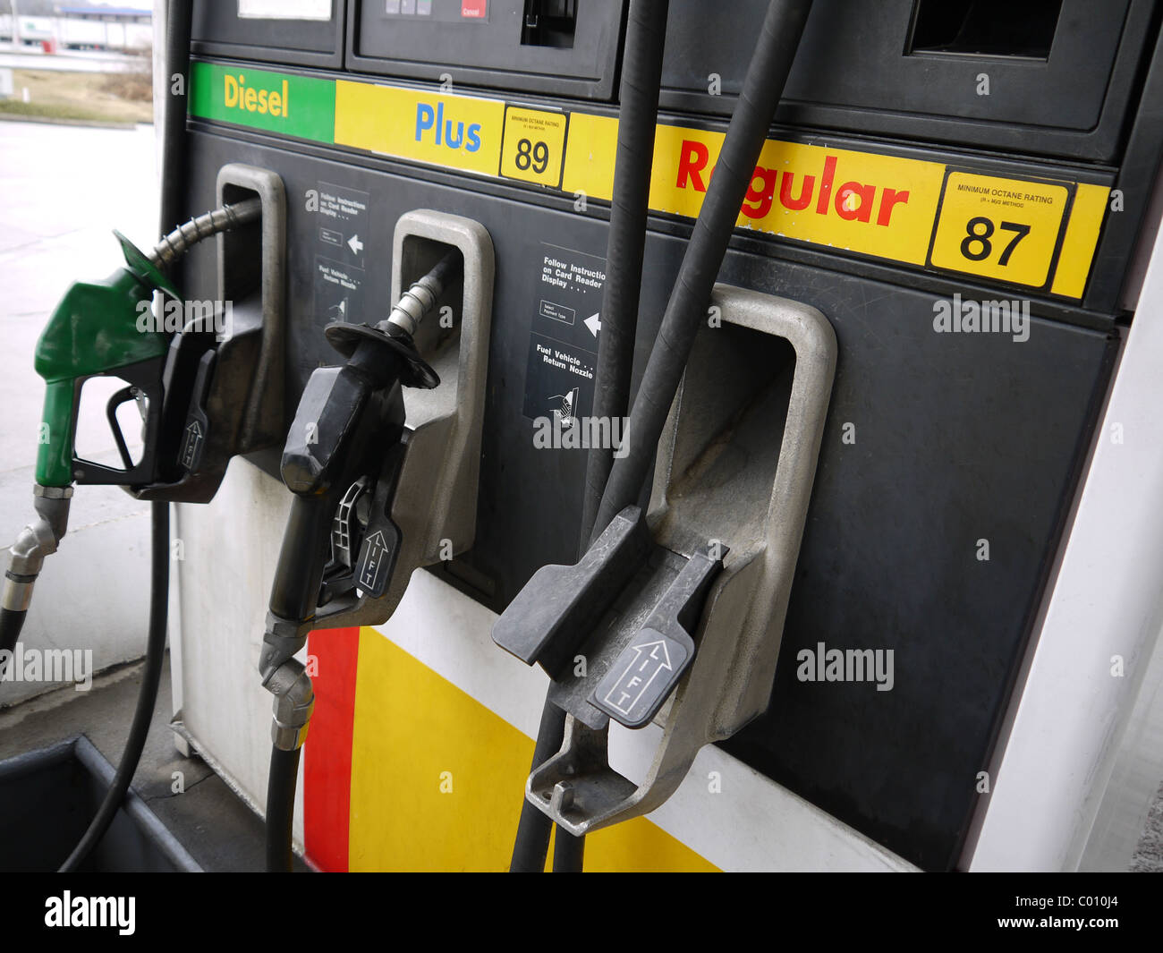 Close-up of gas pump nozzles at a gas station. - Stock Image