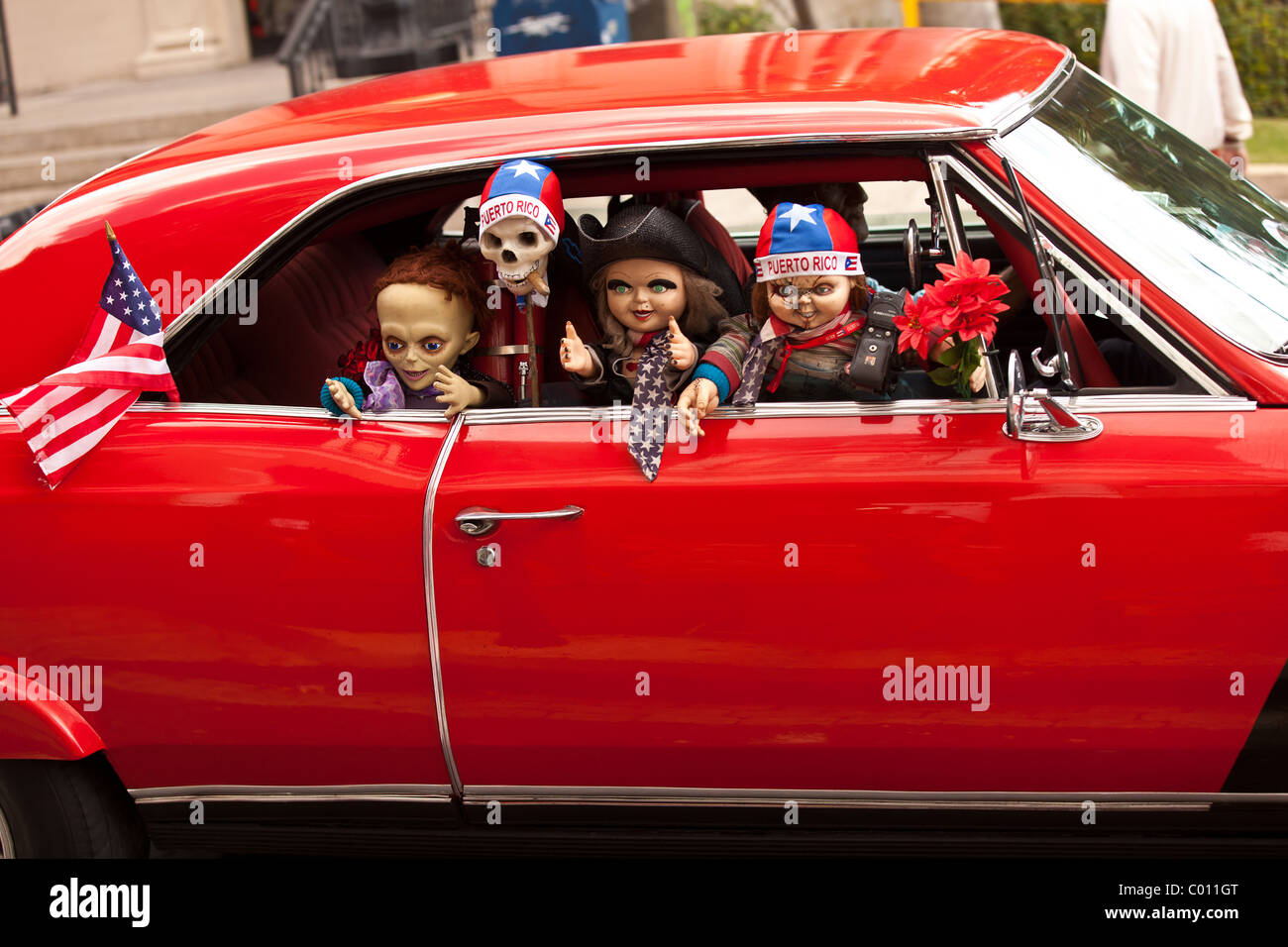 A vintage muscle car decorated with dolls and flags in Old San Juan, Puerto Rico. - Stock Image