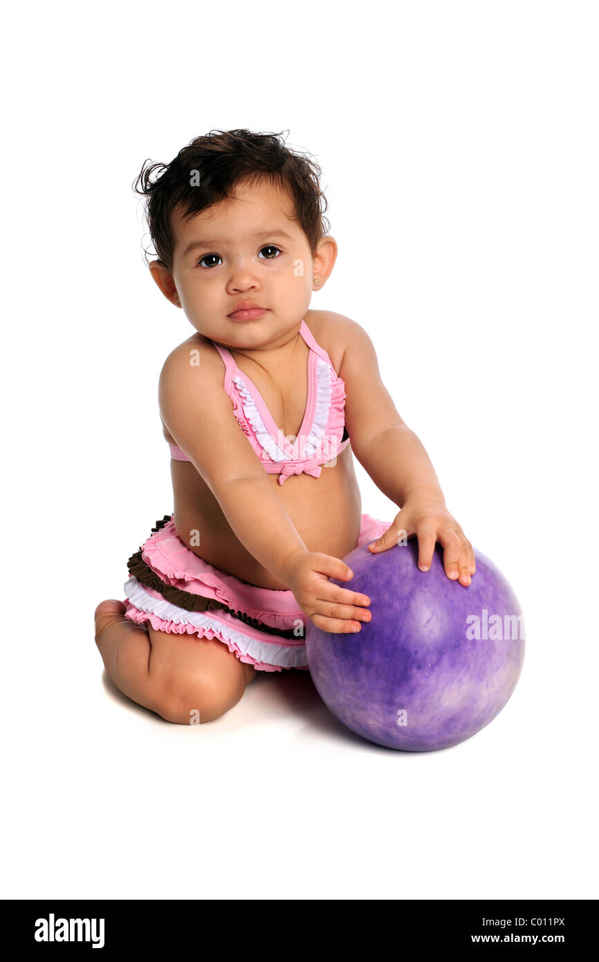 Hispanic girl dressed in bikini playing with ball isolated over white background - Stock Image