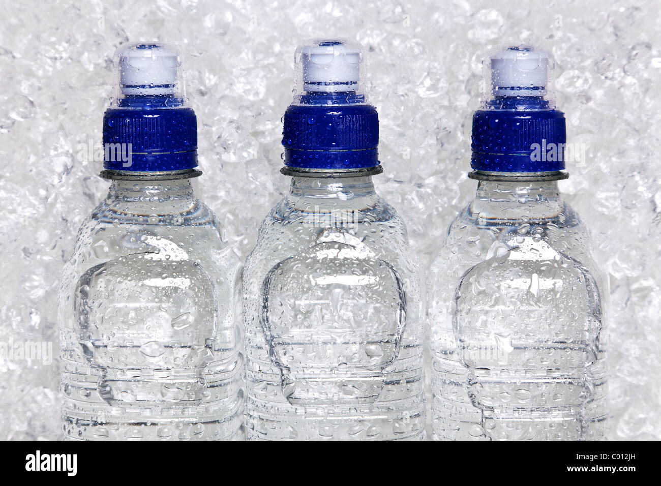 Photo of cold mineral water in plastic bottles on crushed ice - Stock Image