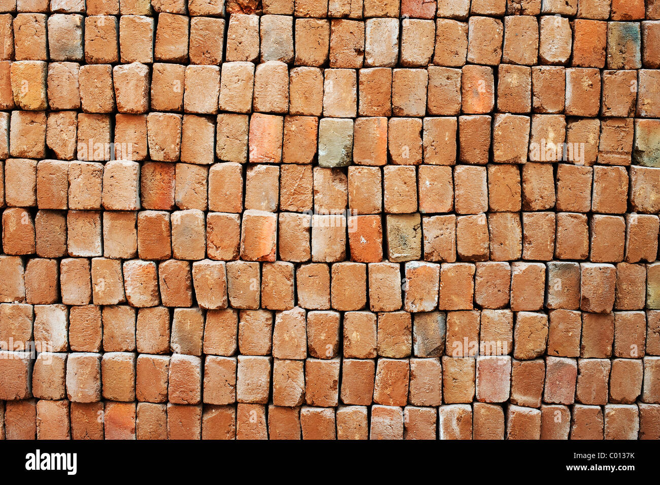 Pile of hand made bricks pattern. India - Stock Image