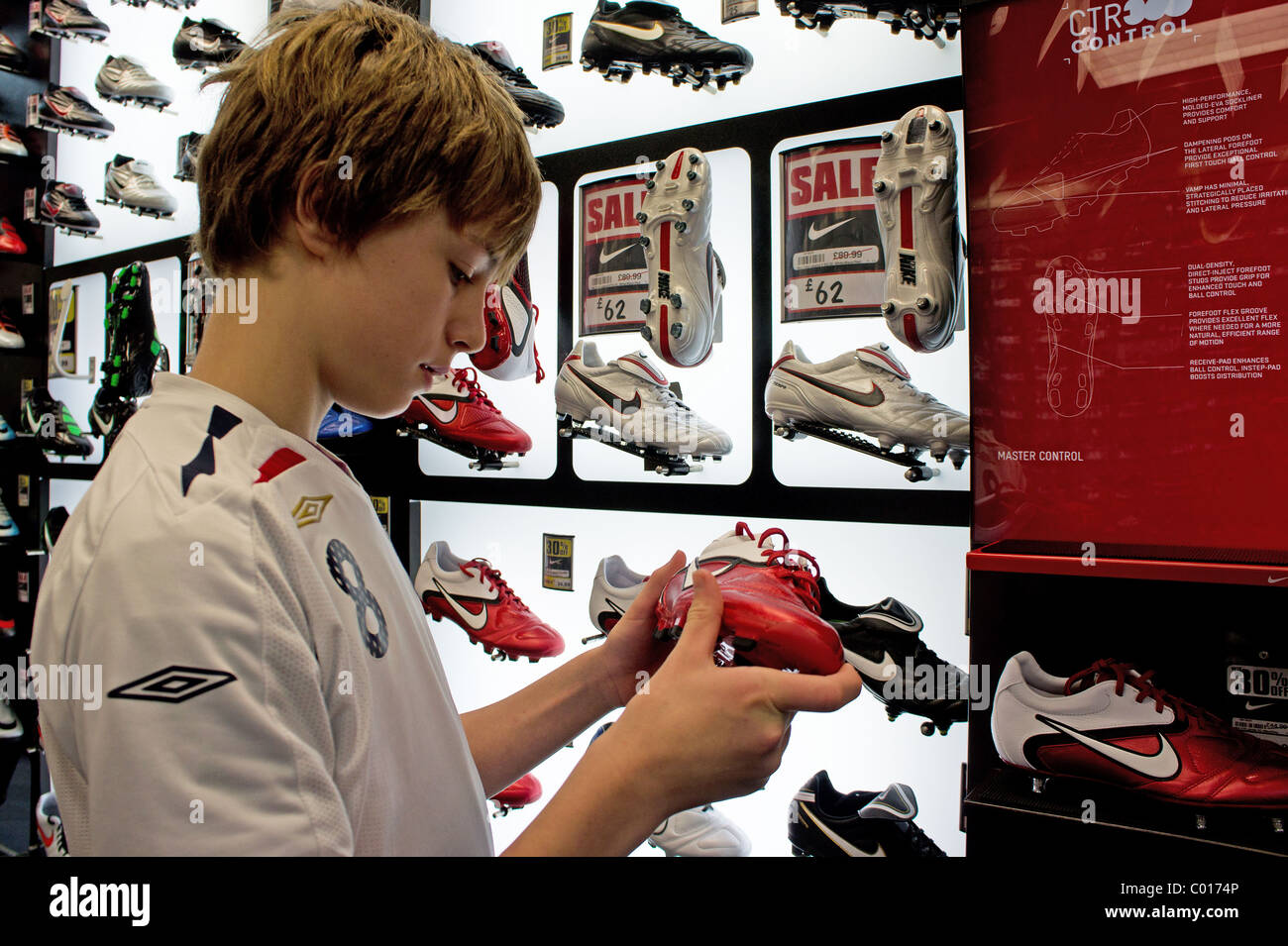 a teenage boy looking at football boots in a sporting goods shop, uk - Stock Image