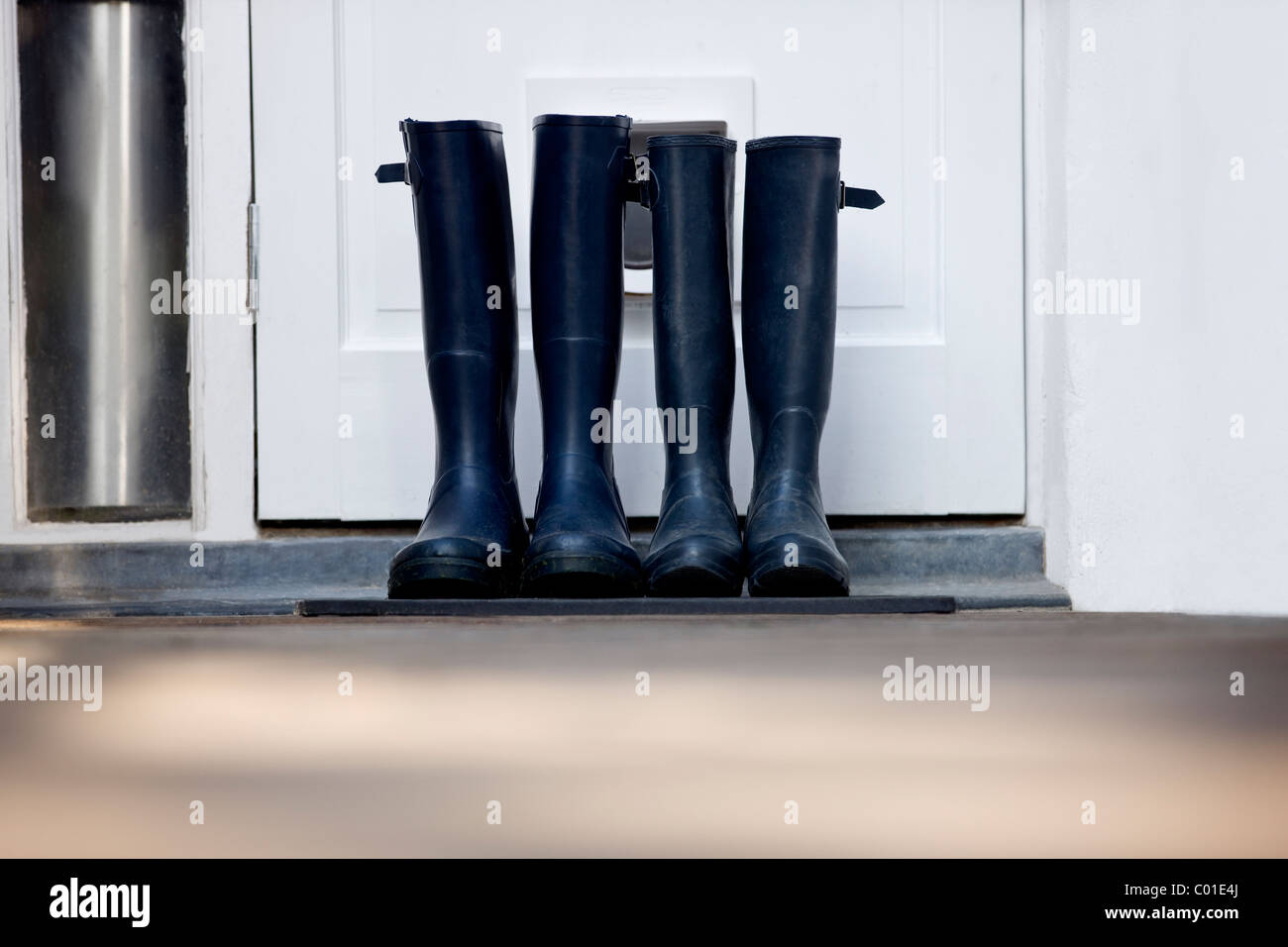 Two pairs of Wellington boots by a door - Stock Image