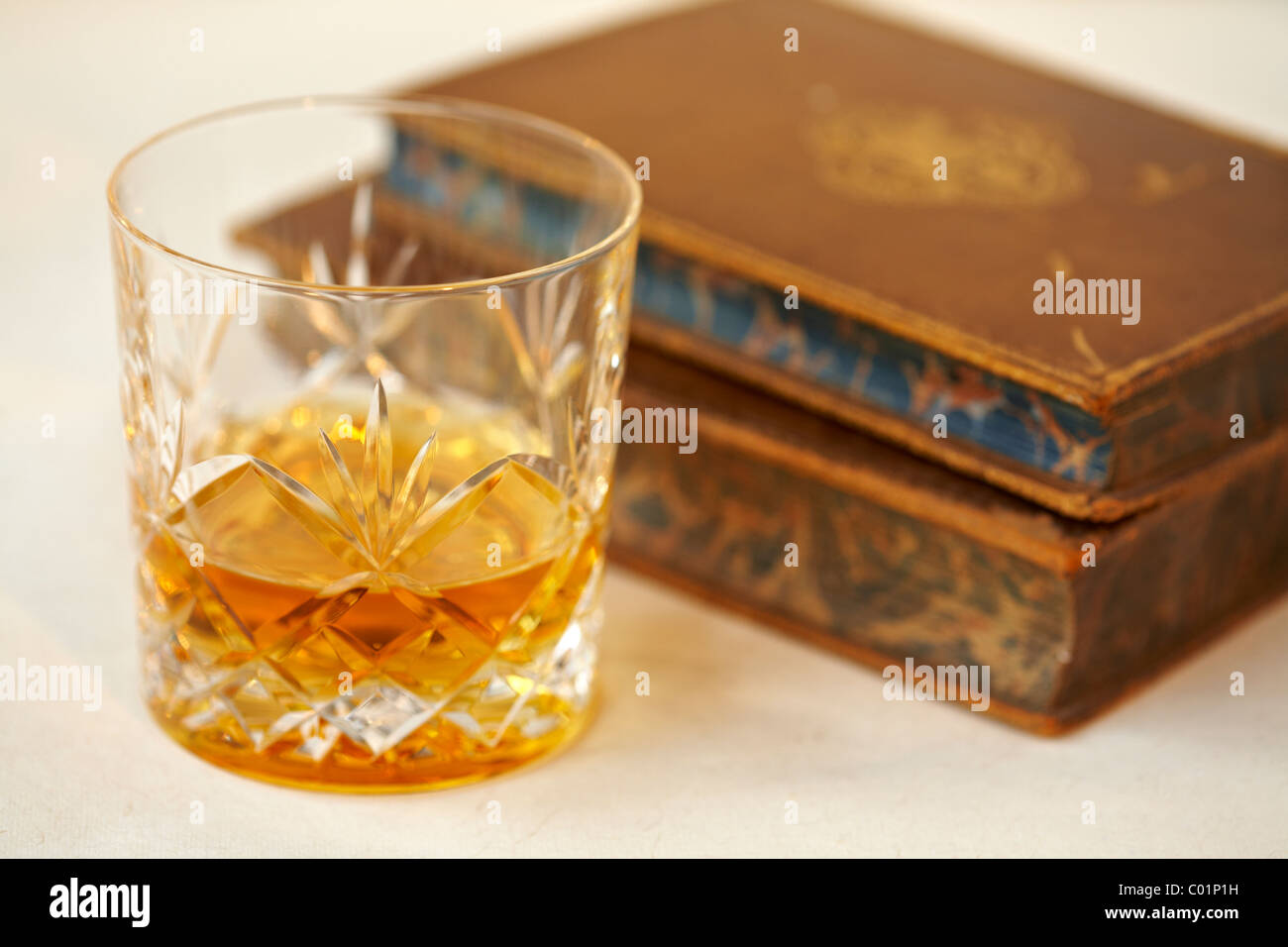 Glass of  malt whisky and old antique books - Stock Image