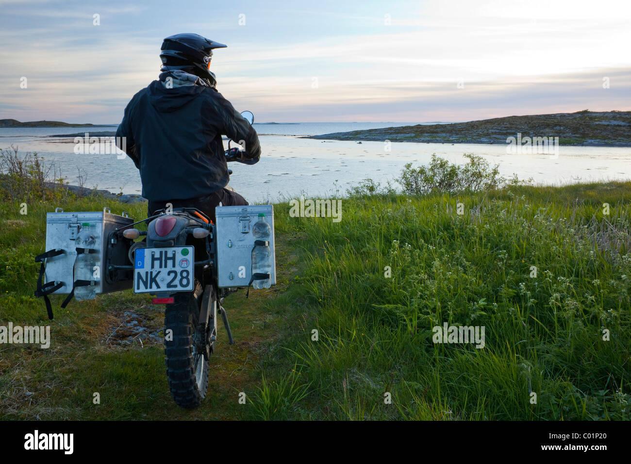 Man riding an Enduro motorcycle in the evening twilight, Gimsefjorde, Norway, Scandinavia, Europe Stock Photo