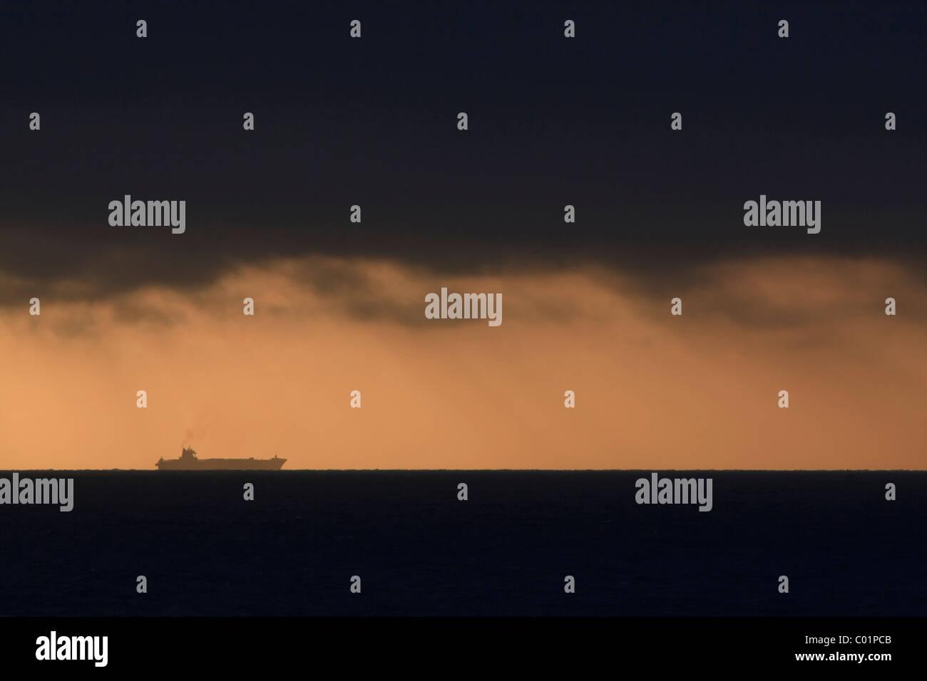 Large container ship on the darkened horizon at sunset, Hirtshals, Denmark, Scandinavia, Europe - Stock Image